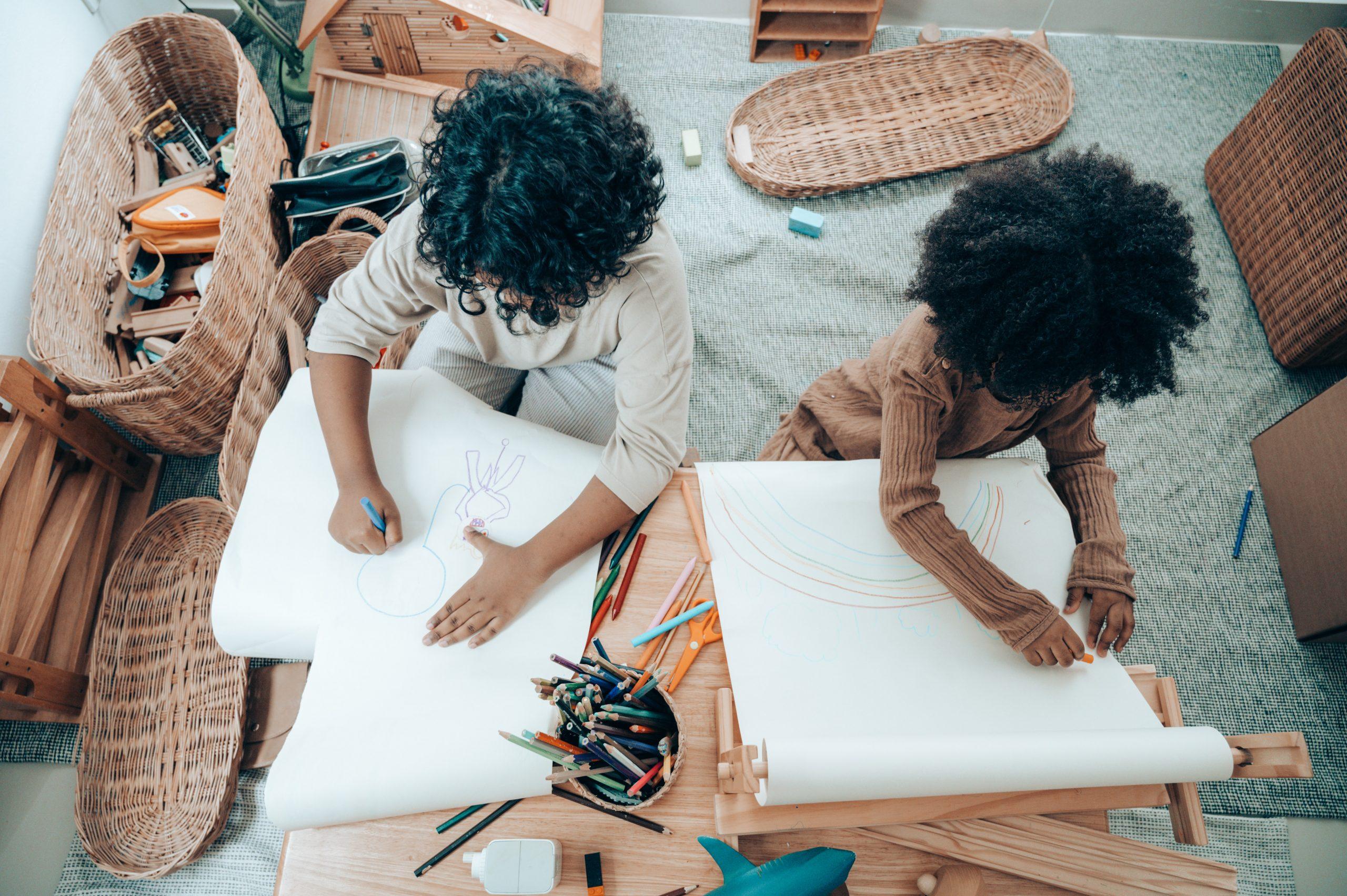 Duas crianças vistas de cima desenhando.