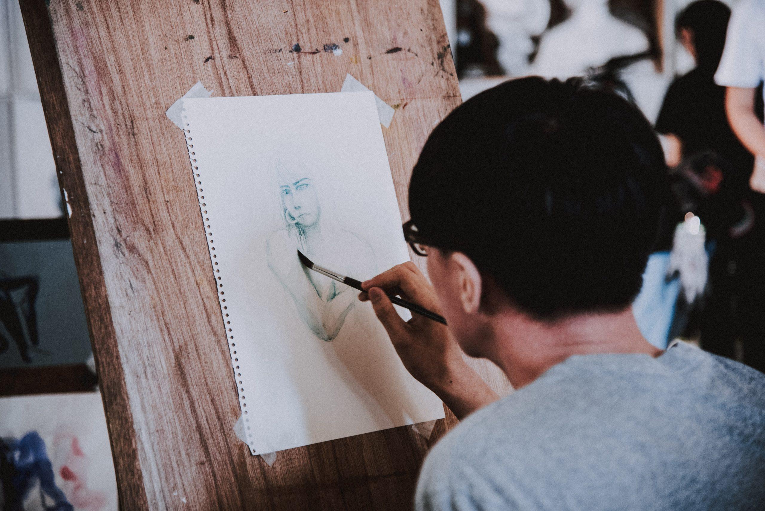 Imagem de uma pessoa desenhando na prancheta.