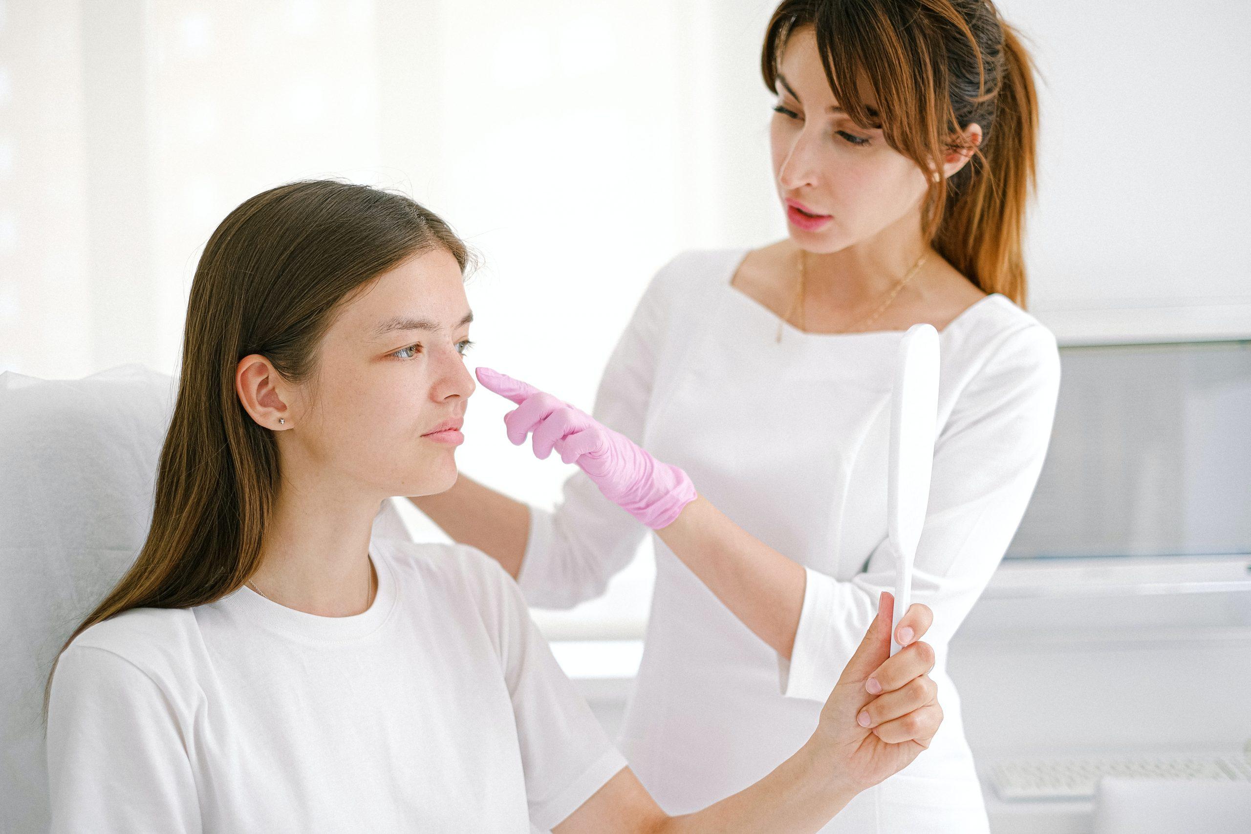Imagem de uma profissional realizando um tratamento estético em uma jovem.
