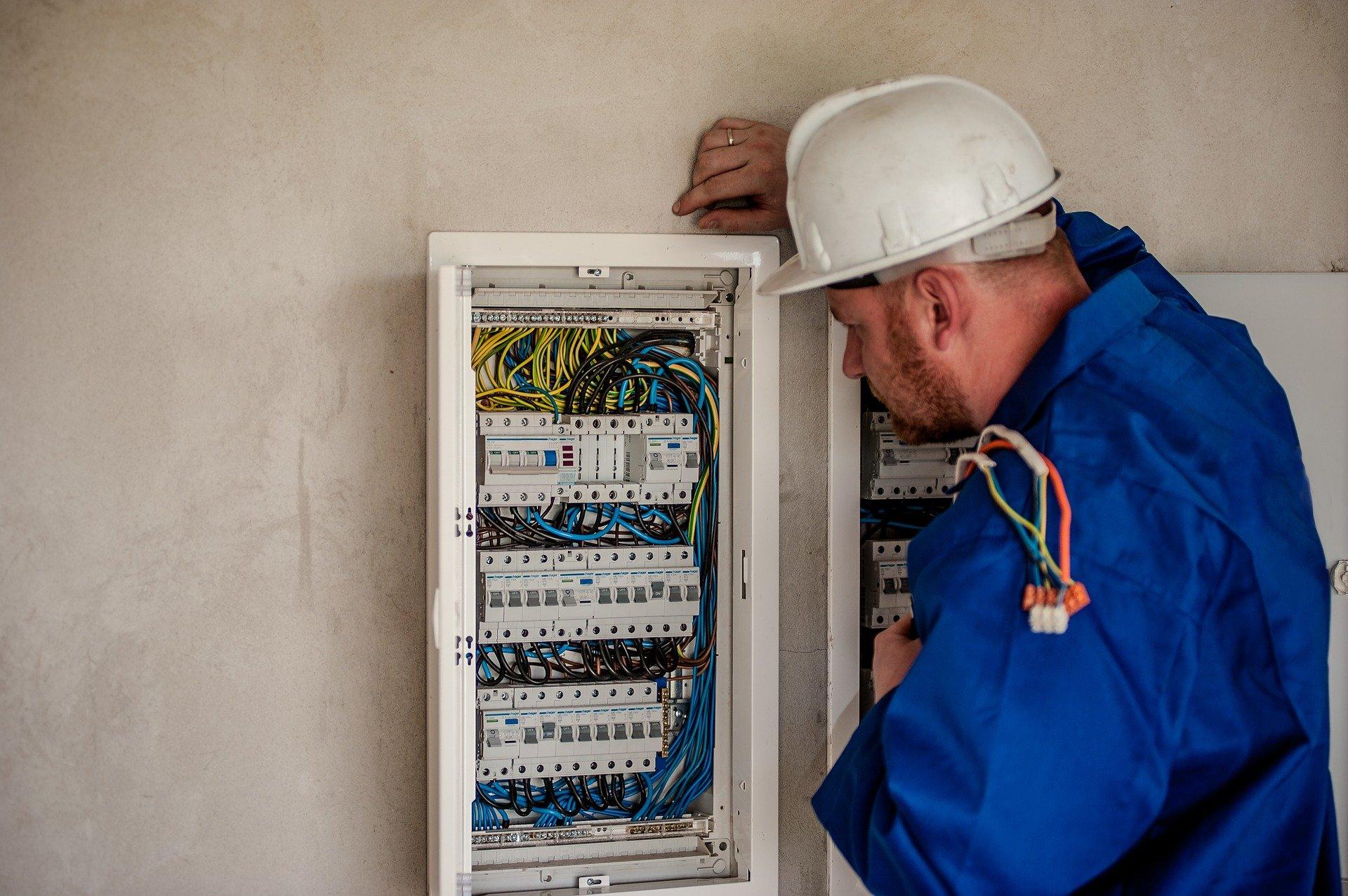 Imagem mostra um eletricista mexendo em um quadro de distribuição.