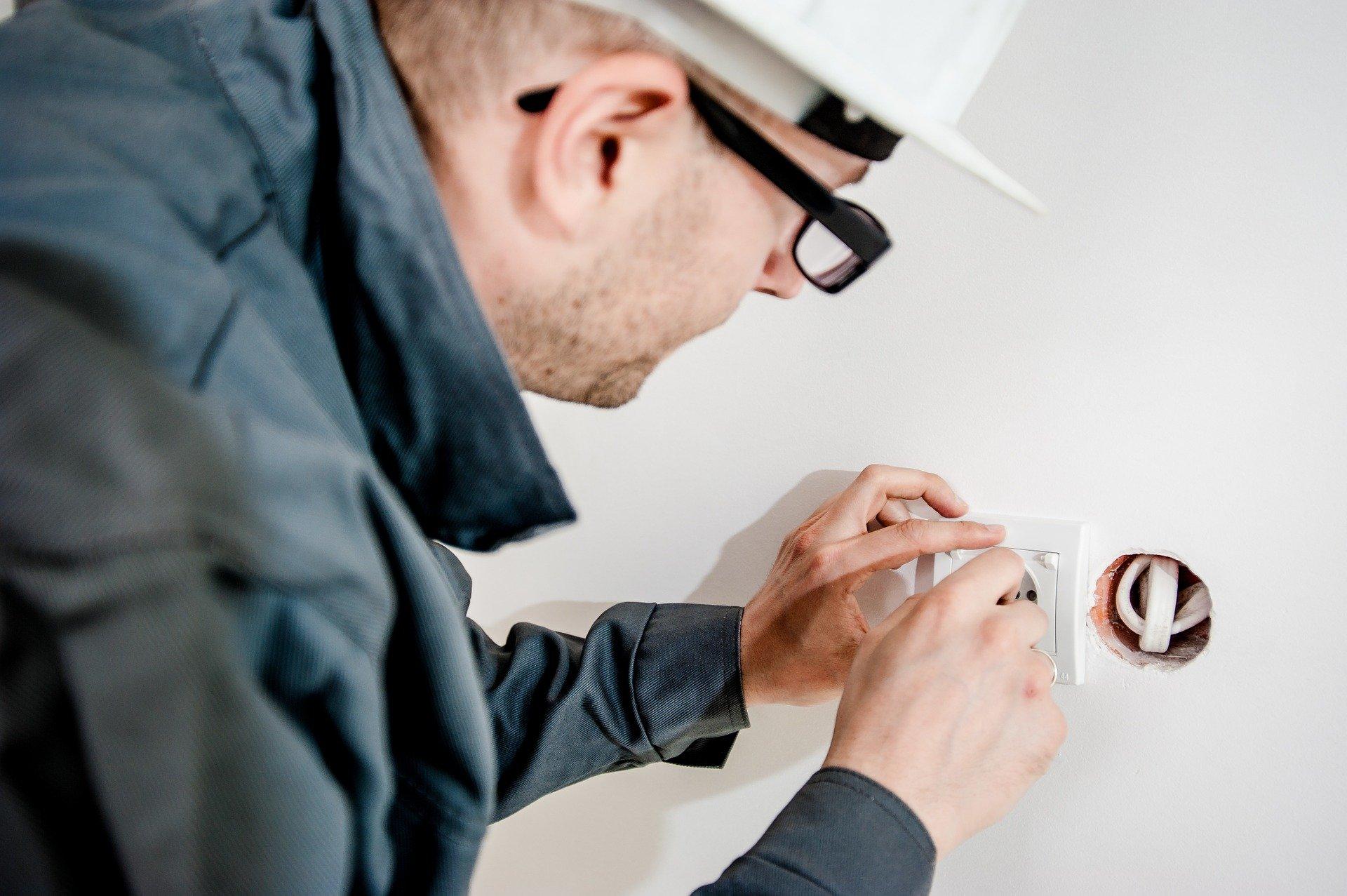 Imagem mostra um eletricista fazendo um serviço doméstico.