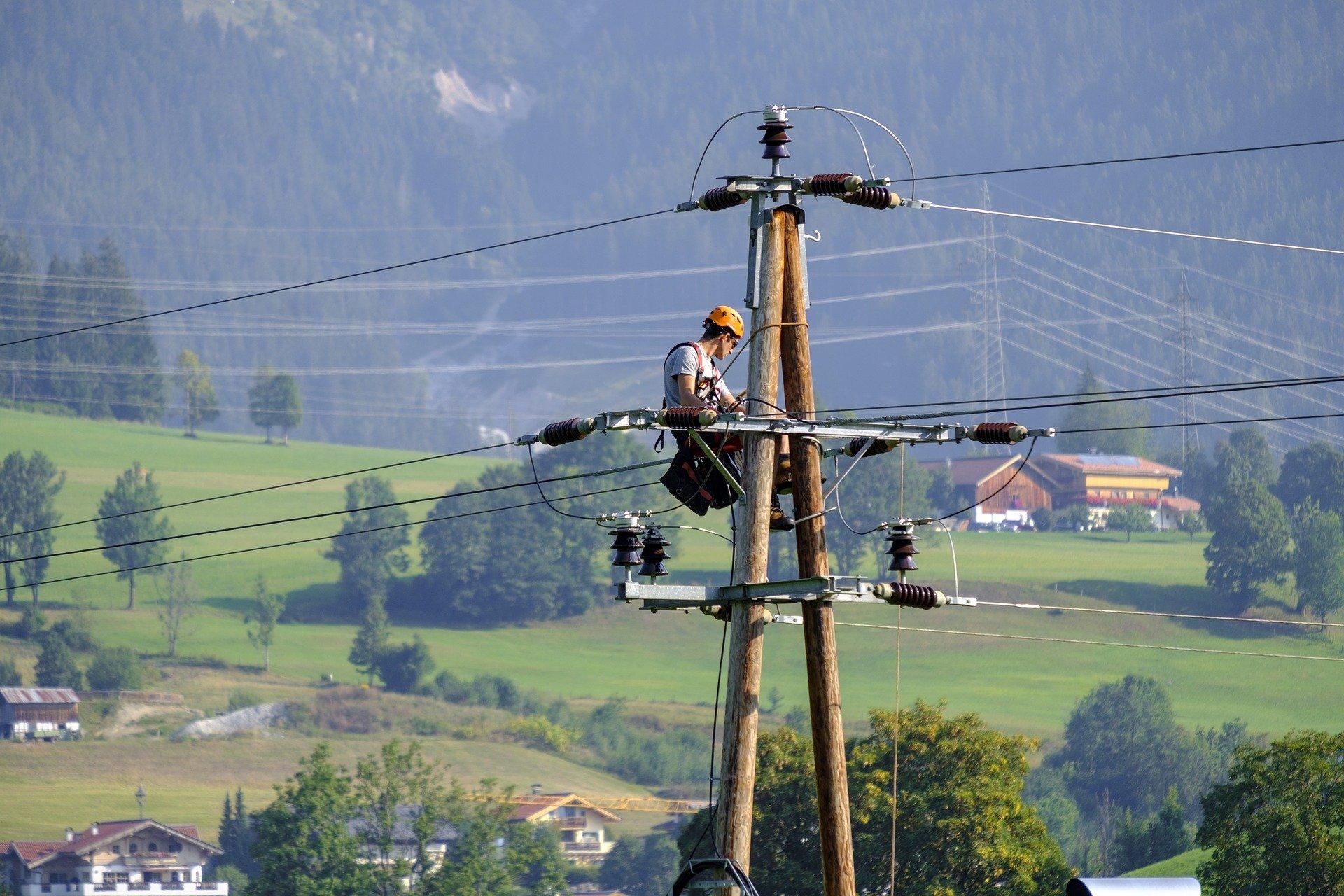 Imagem mostra um eletricista fazendo um reparo em um poste.