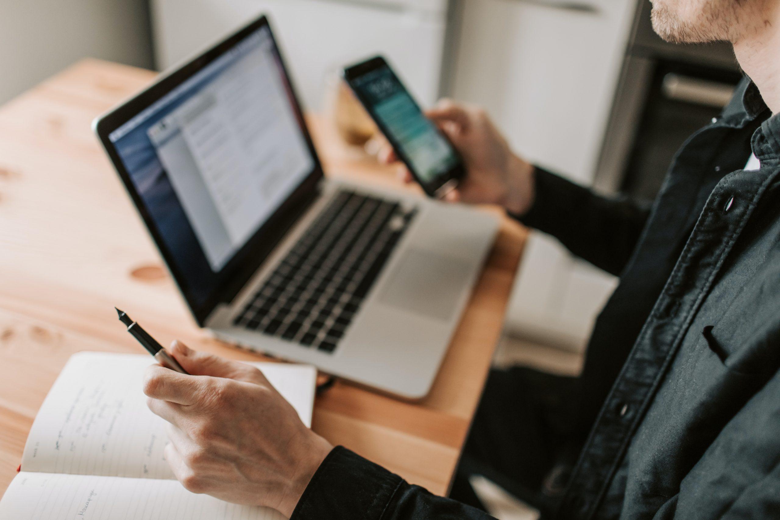 Imagem desfocada, sentado na mesa com computador , caderno e celular.