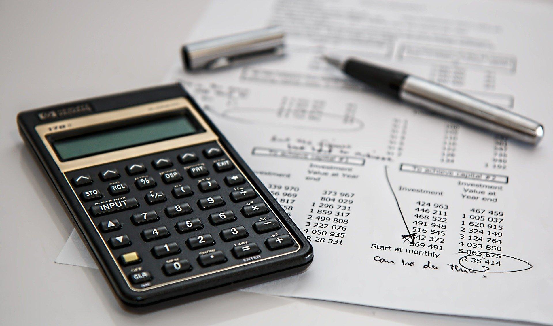 Imagem mostra uma calculadora sobre algumas folhas de papel com números.