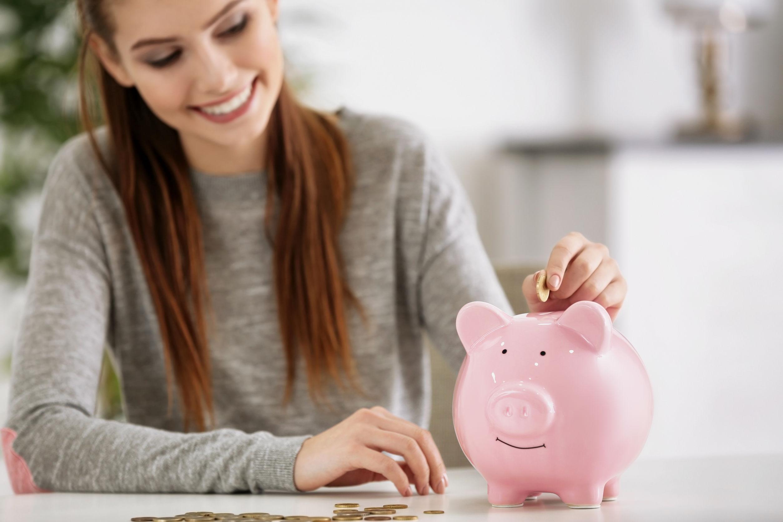 Imagem mostra uma mulher olhando para um cofre em forma de porquinho.