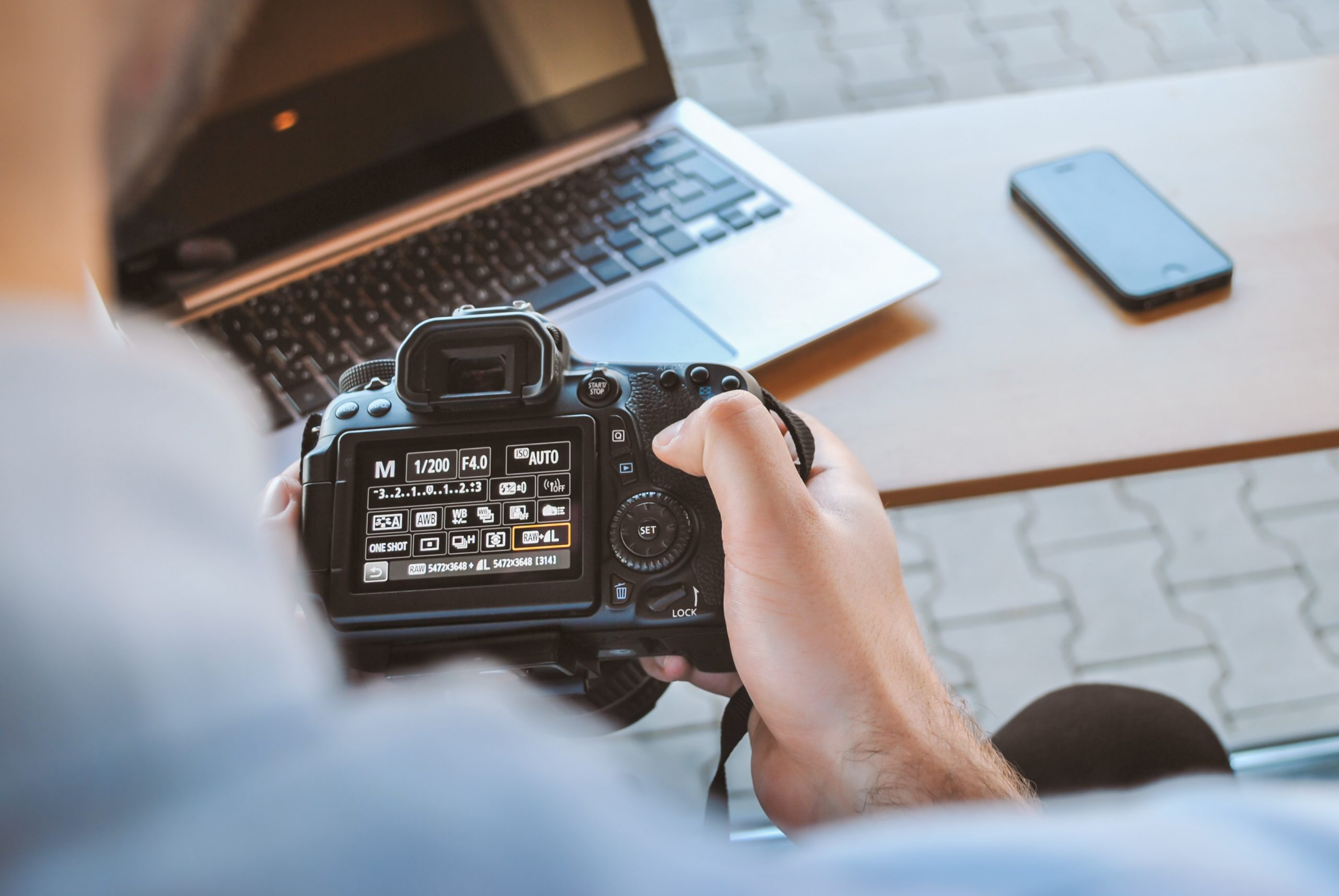 mão segurando câmera profissional com notebook ao fundo