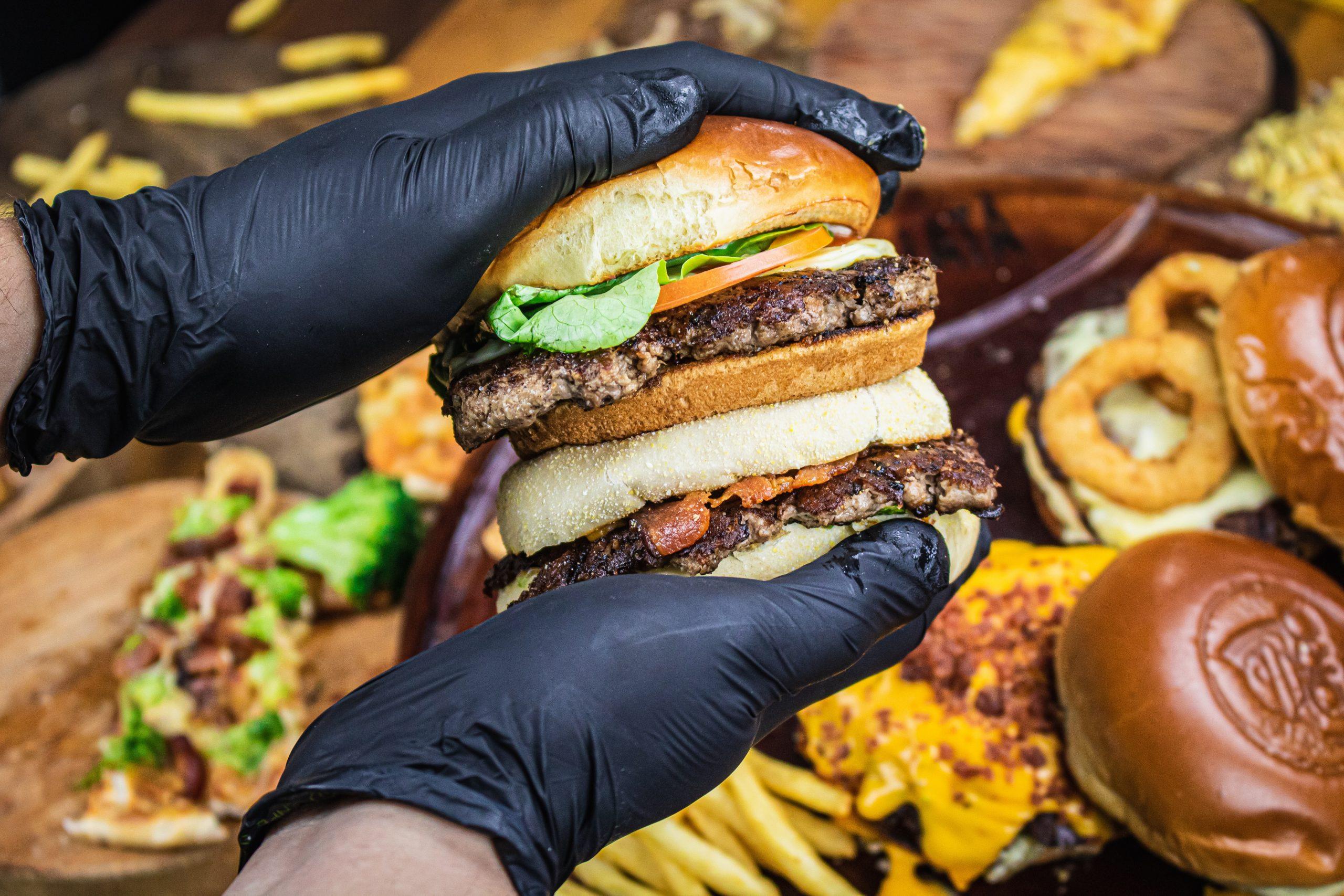 Hambúrguer completo sendo amassado com a mão, um smash burguer.