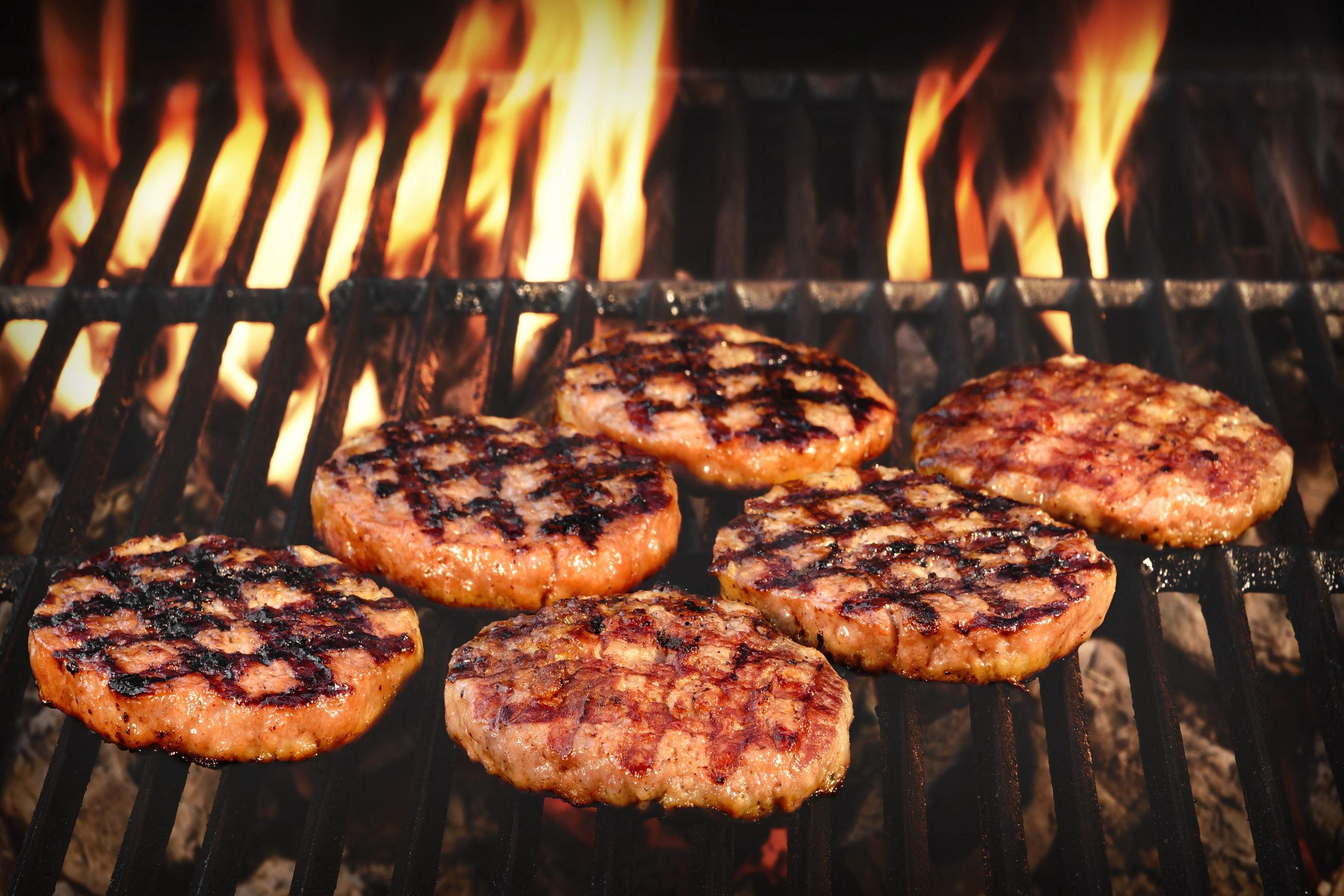 Vários hambúrgueres sendo feitos em uma grelha