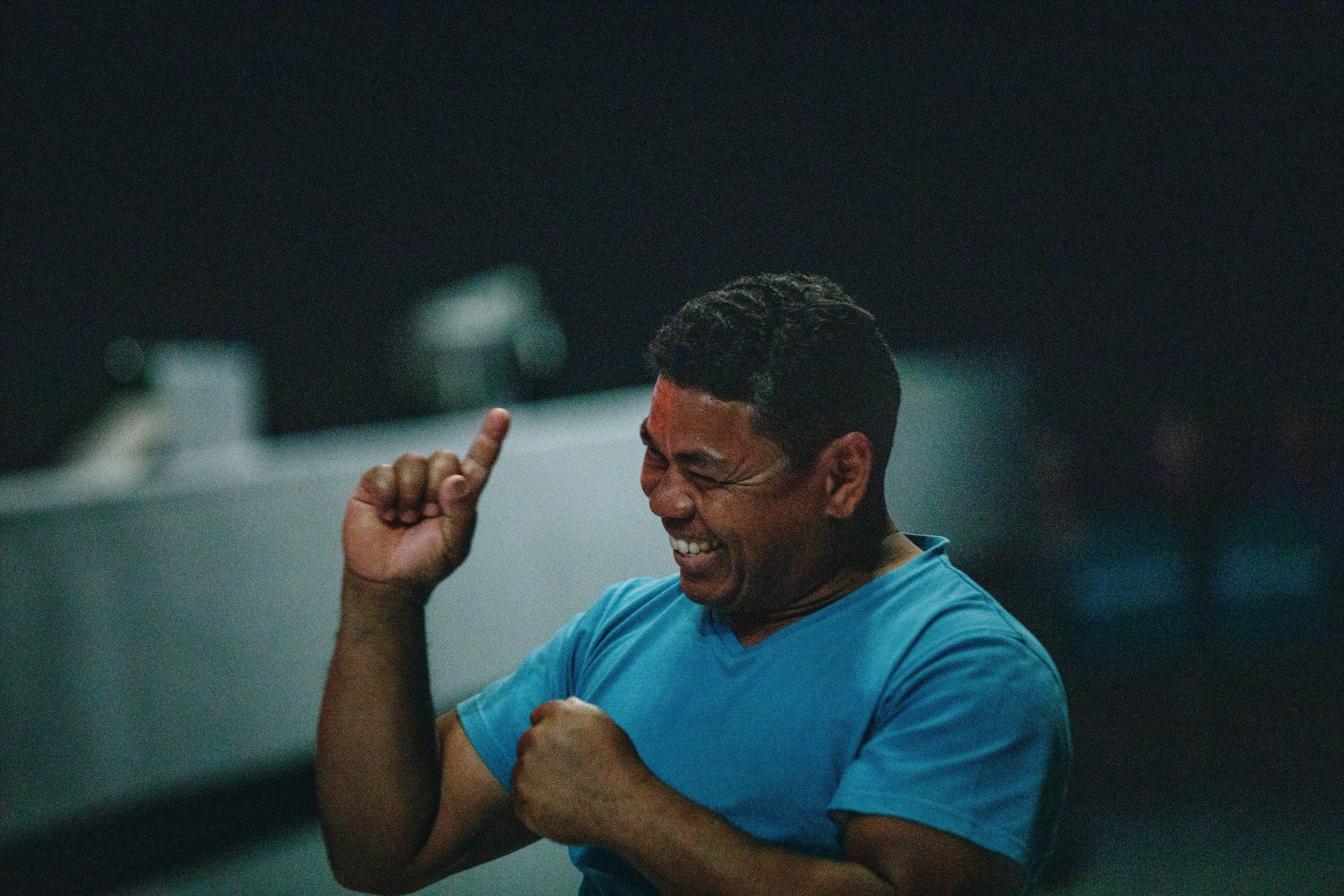 Na foto um homem sorrindo usando blusa azul.