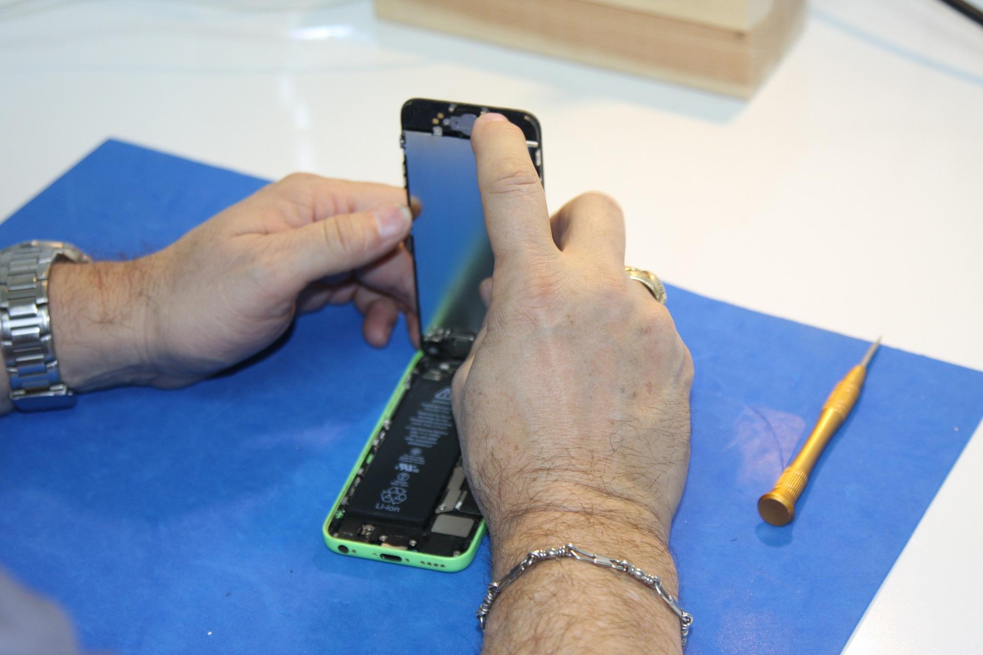Imagem mostra uma pessoa mexendo em um celular aberto.
