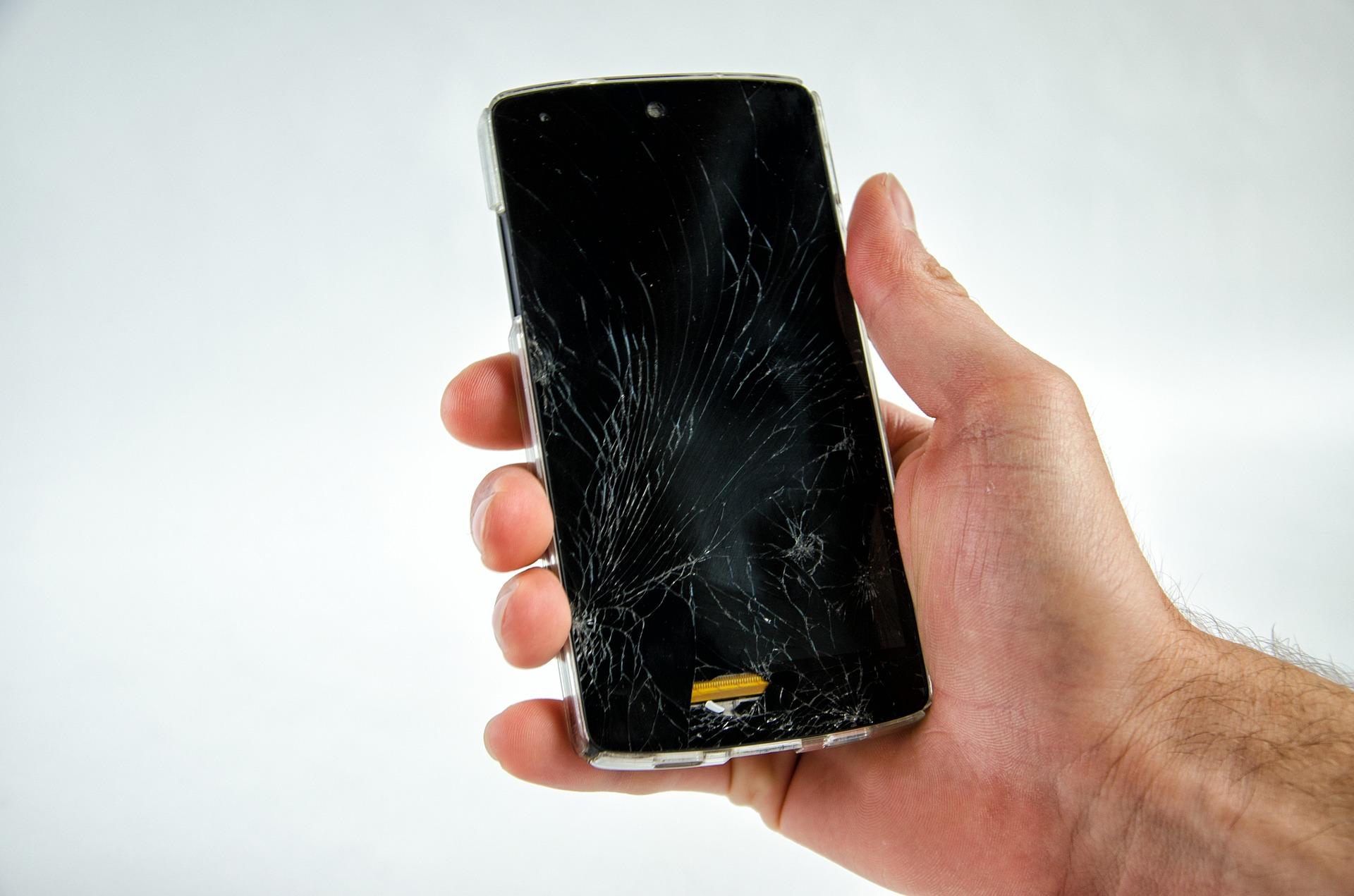 Imagem mostra uma pessoa segurando um celular com a tela quebrada.