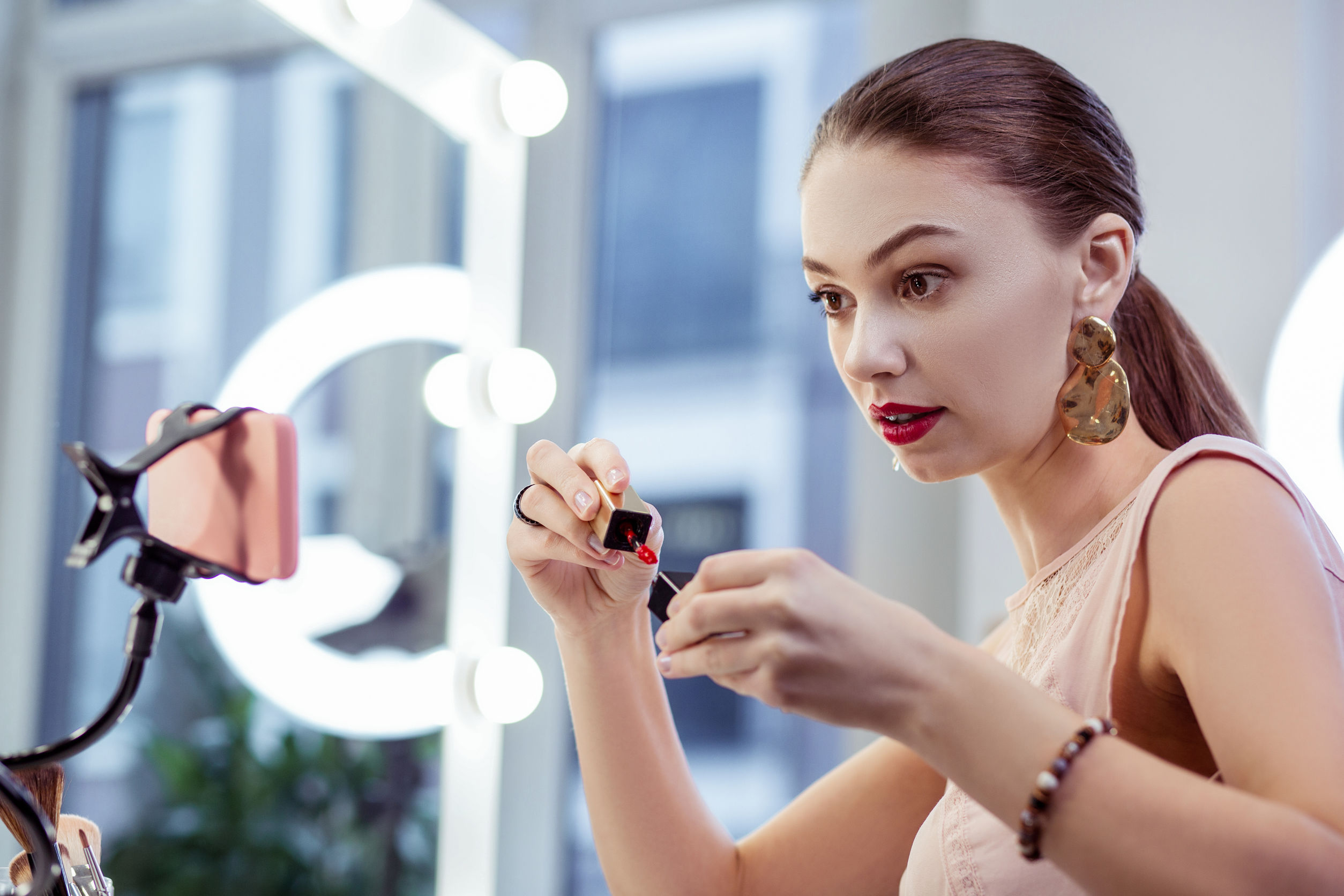 mulher acompanhando um curso de maquiagem pelo smartphone