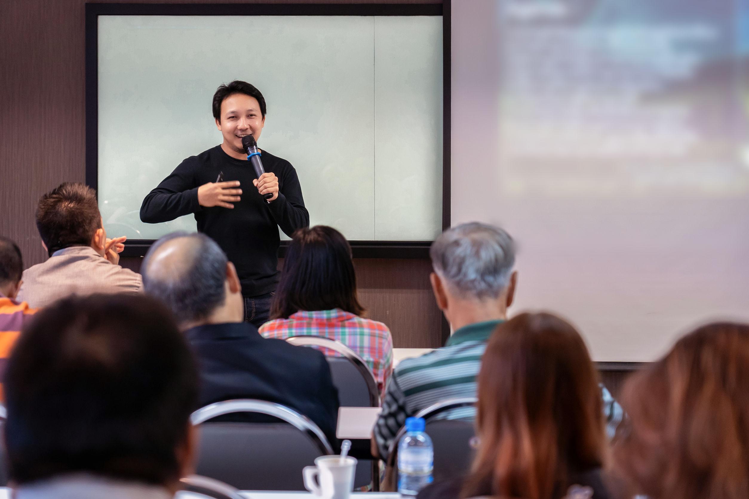 Palestrante asiático sorrindo e discursando na frente de uma sala com vários alunos que estão de costas
