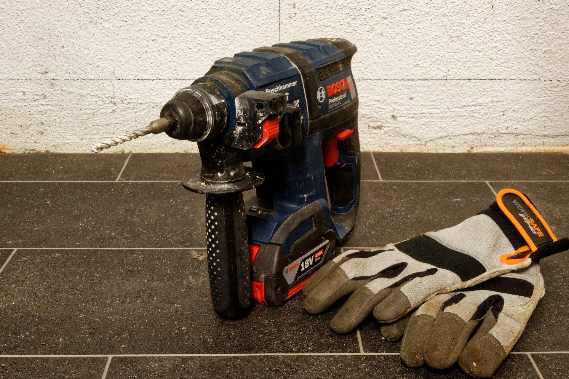 Imagem mostra uma furadeira de impacto Bosch ao lado de um par de luvas.