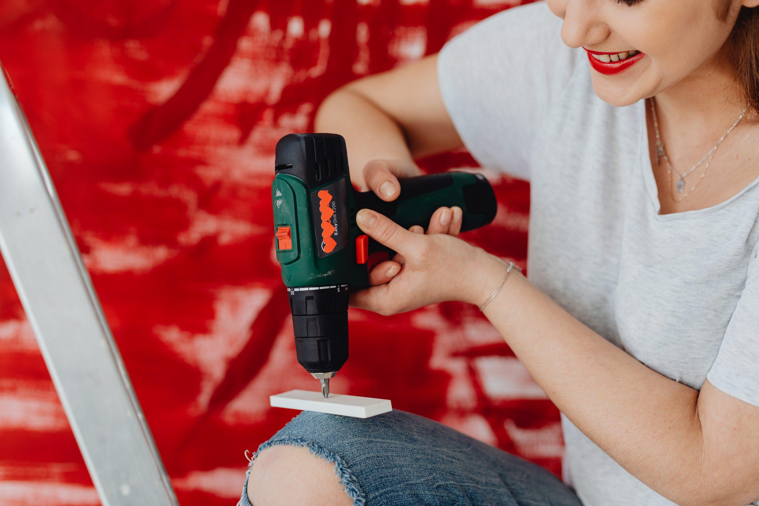 Imagem mostra uma mulher usando uma furadeira Bosch.