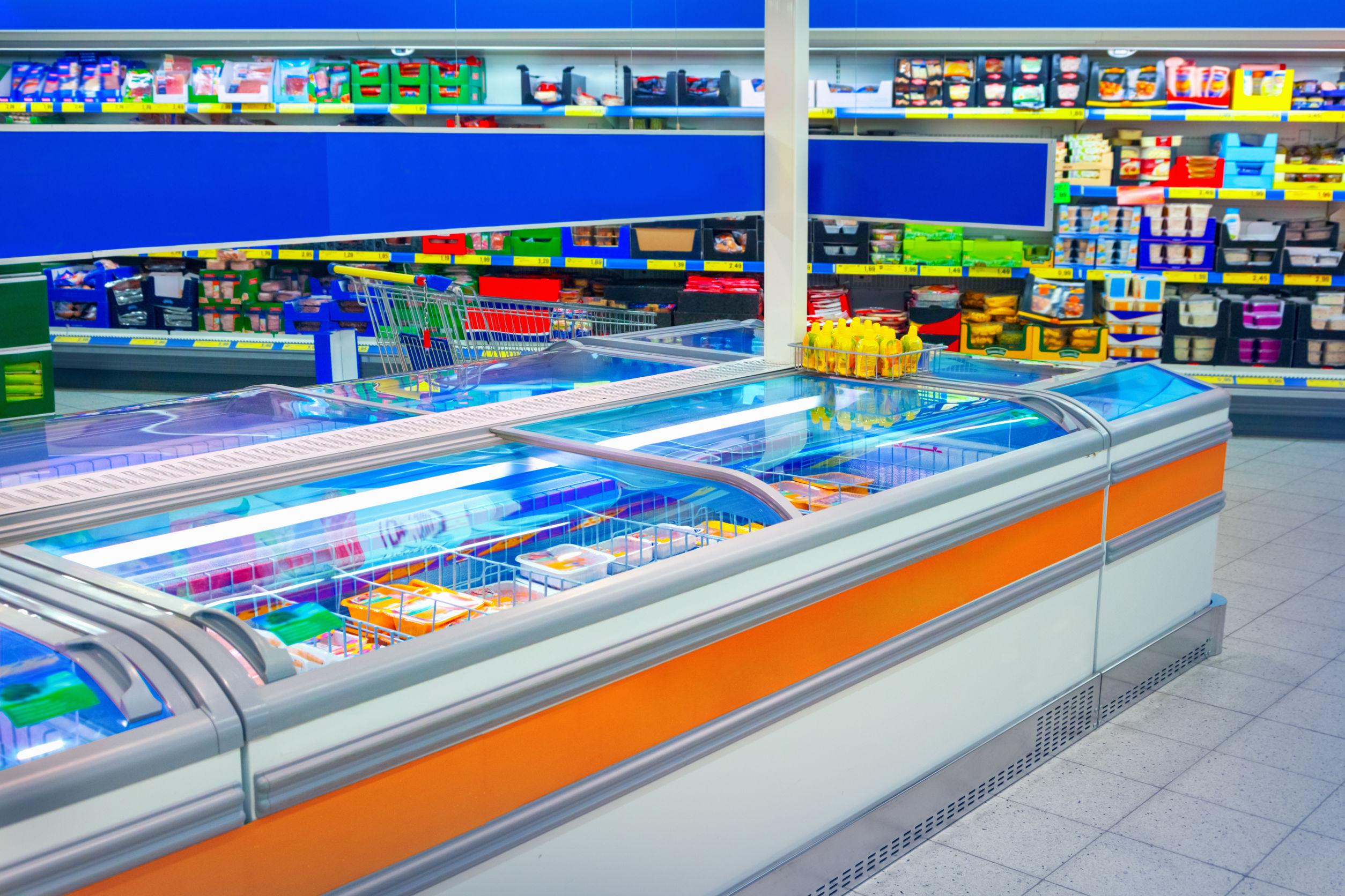 Na foto um corredor de um supermercado com diversos freezers horizontais.