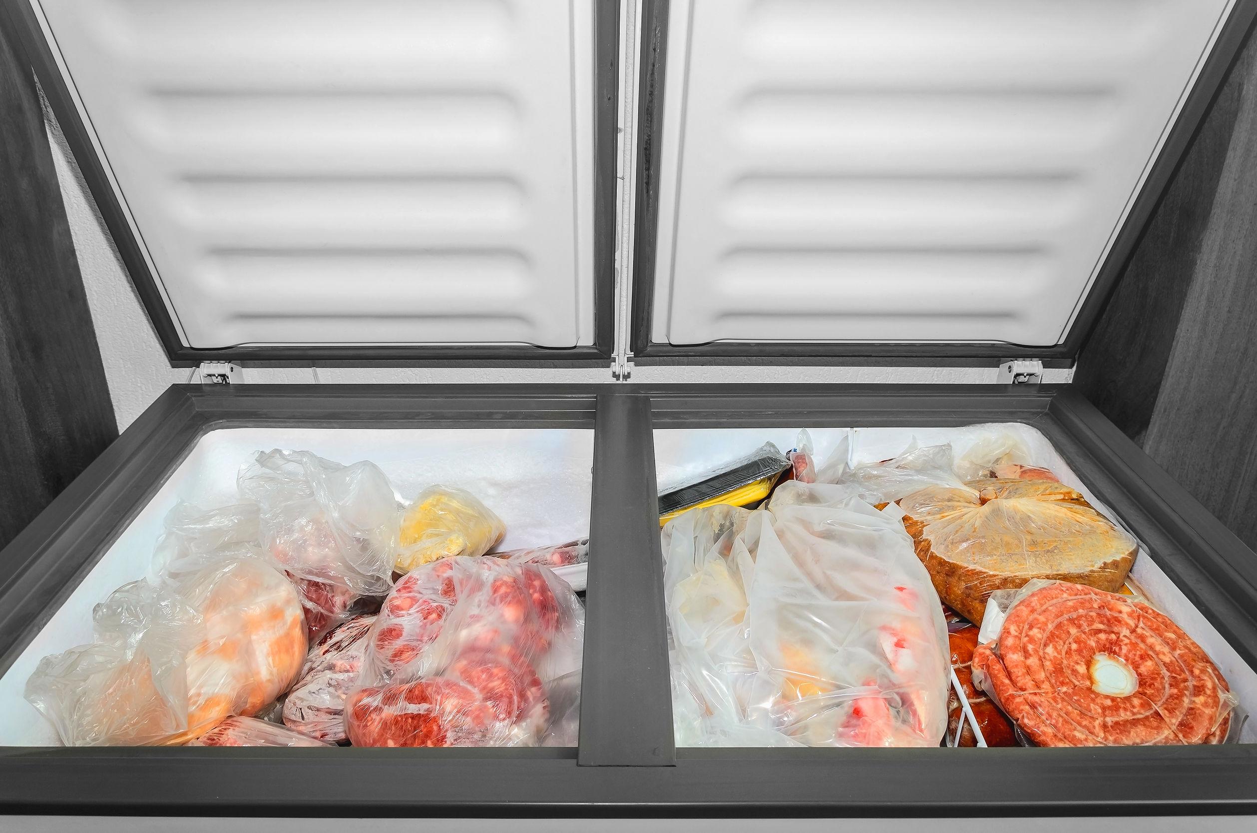 Na foto um freezer horizontal aberto com carnes, pães e linguiças dentro.