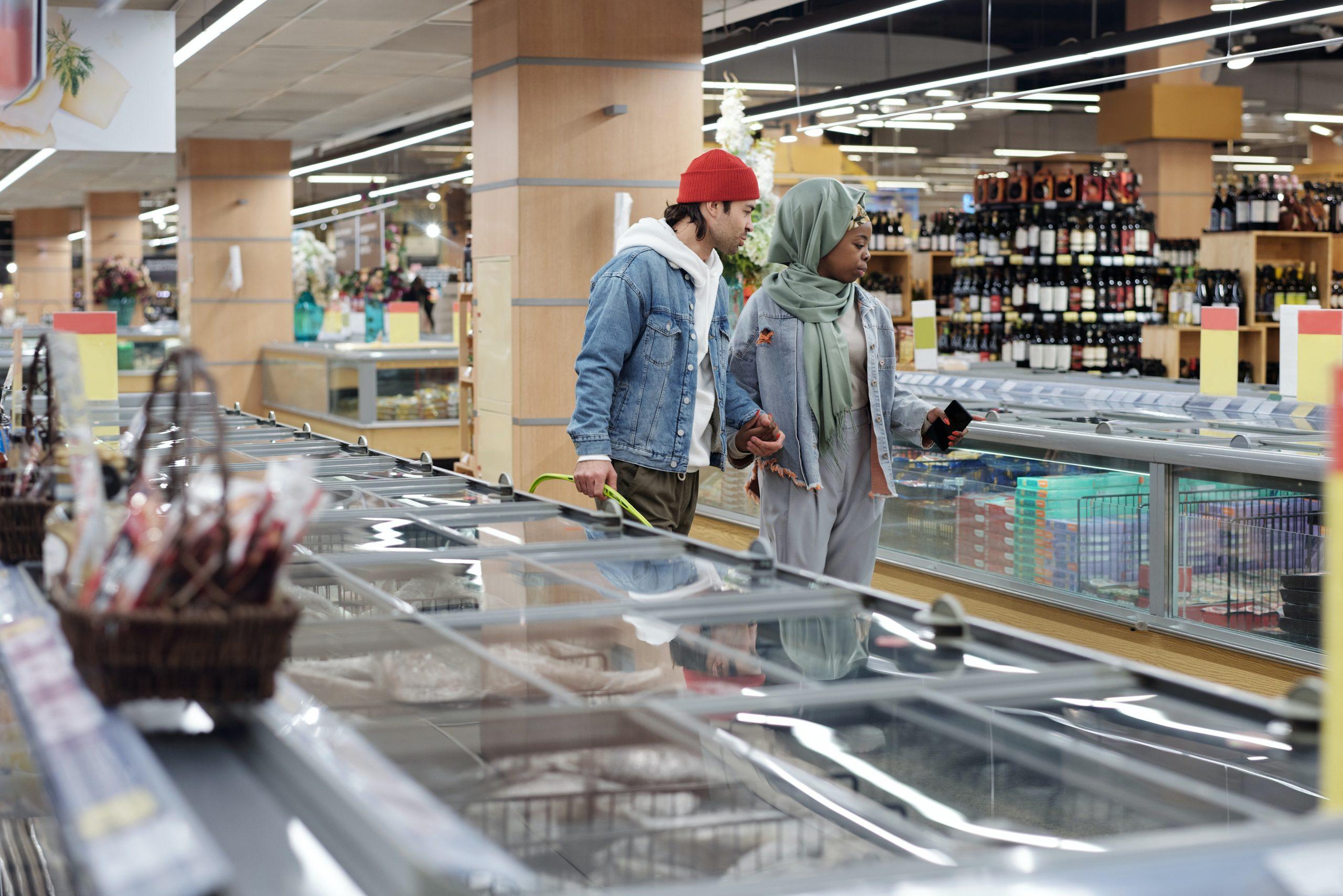 Na foto um casal andando no meio de um corredor de congelados do supermercado.