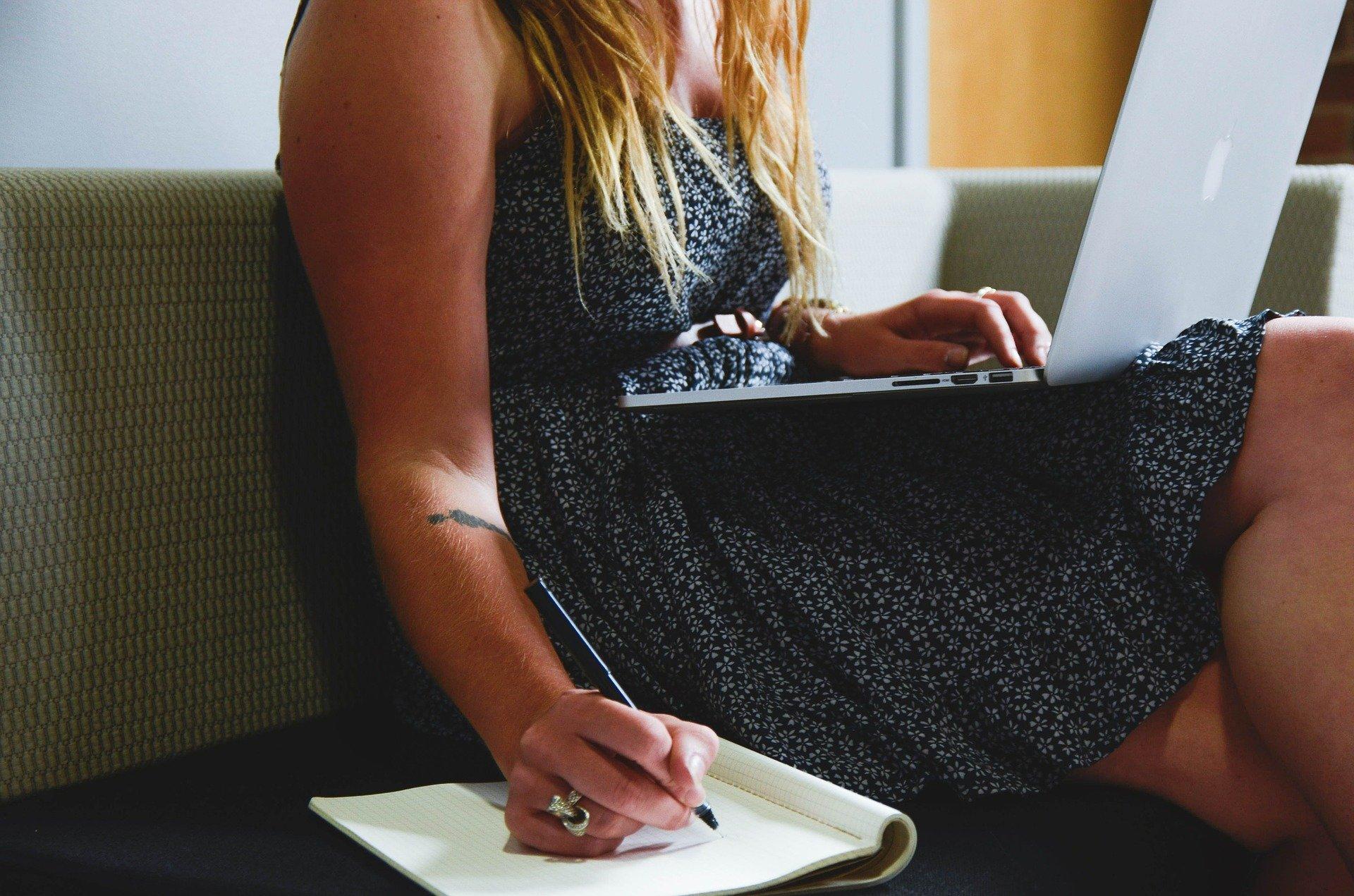 Imagem mostra uma mulher mexendo em um notebook e fazendo anotações.