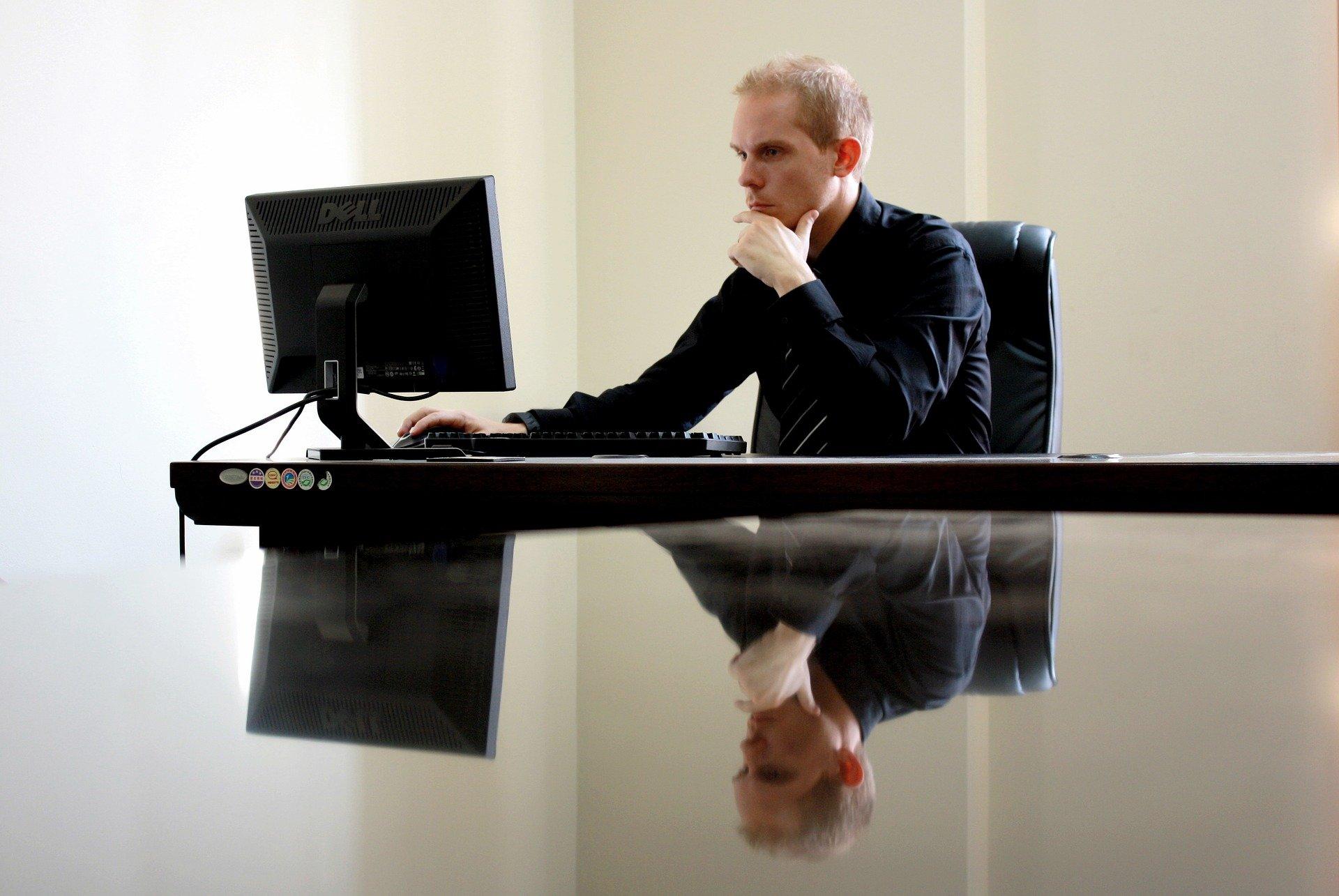 Imagem mostra um homem mexendo em um computador.