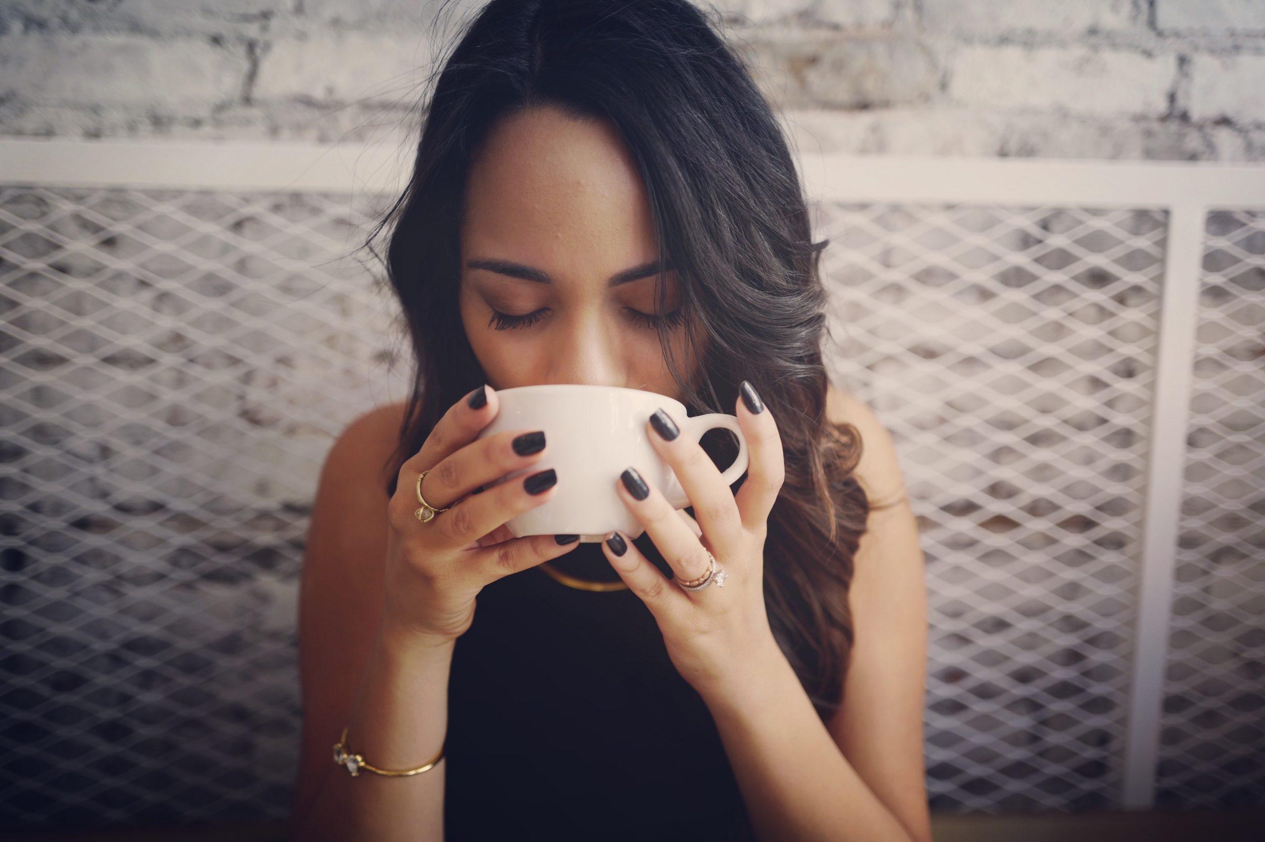 Imagem de uma mulher tomando uma xícara de café.
