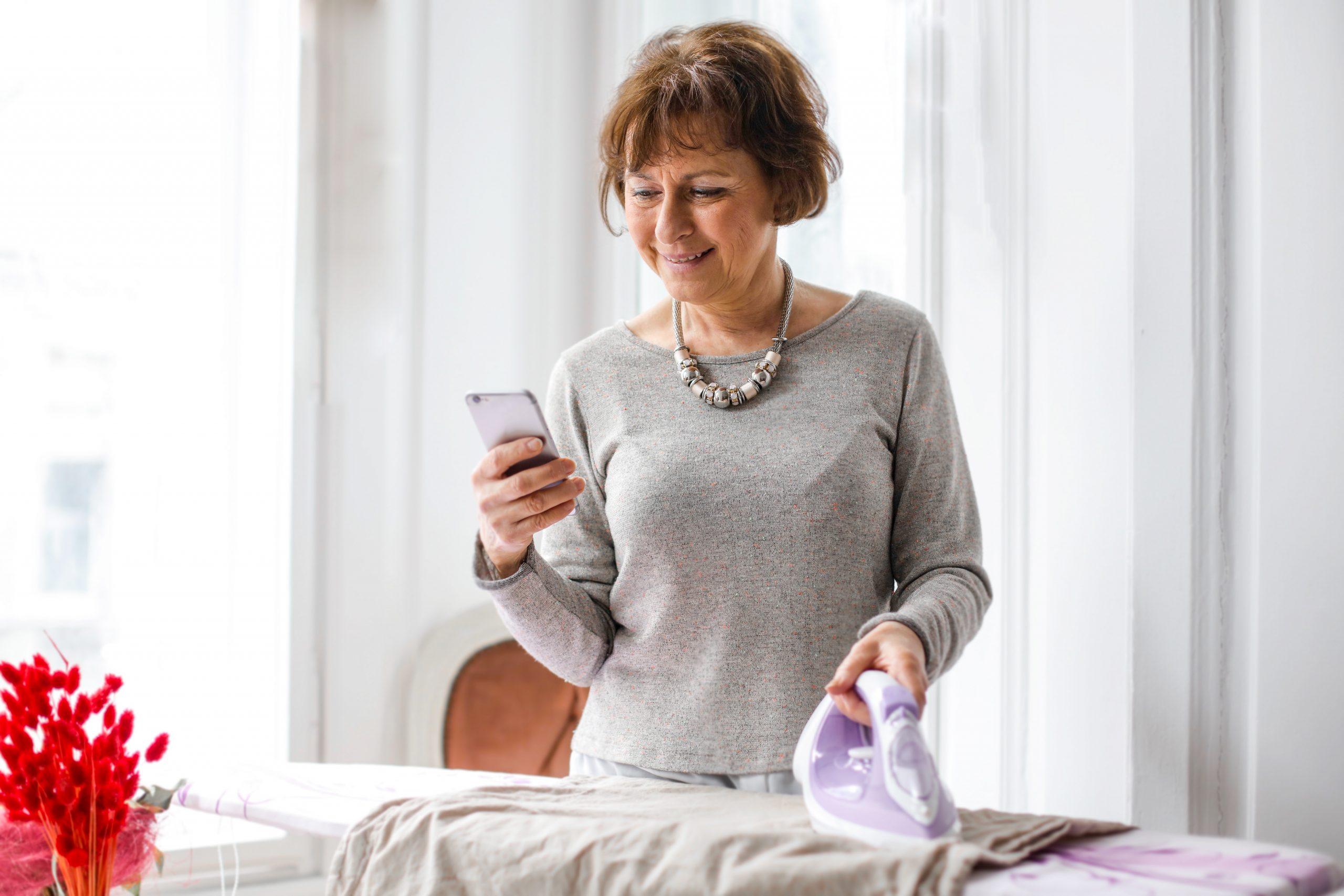 Na foto uma mulher passando roupas segurando um celular na mão.