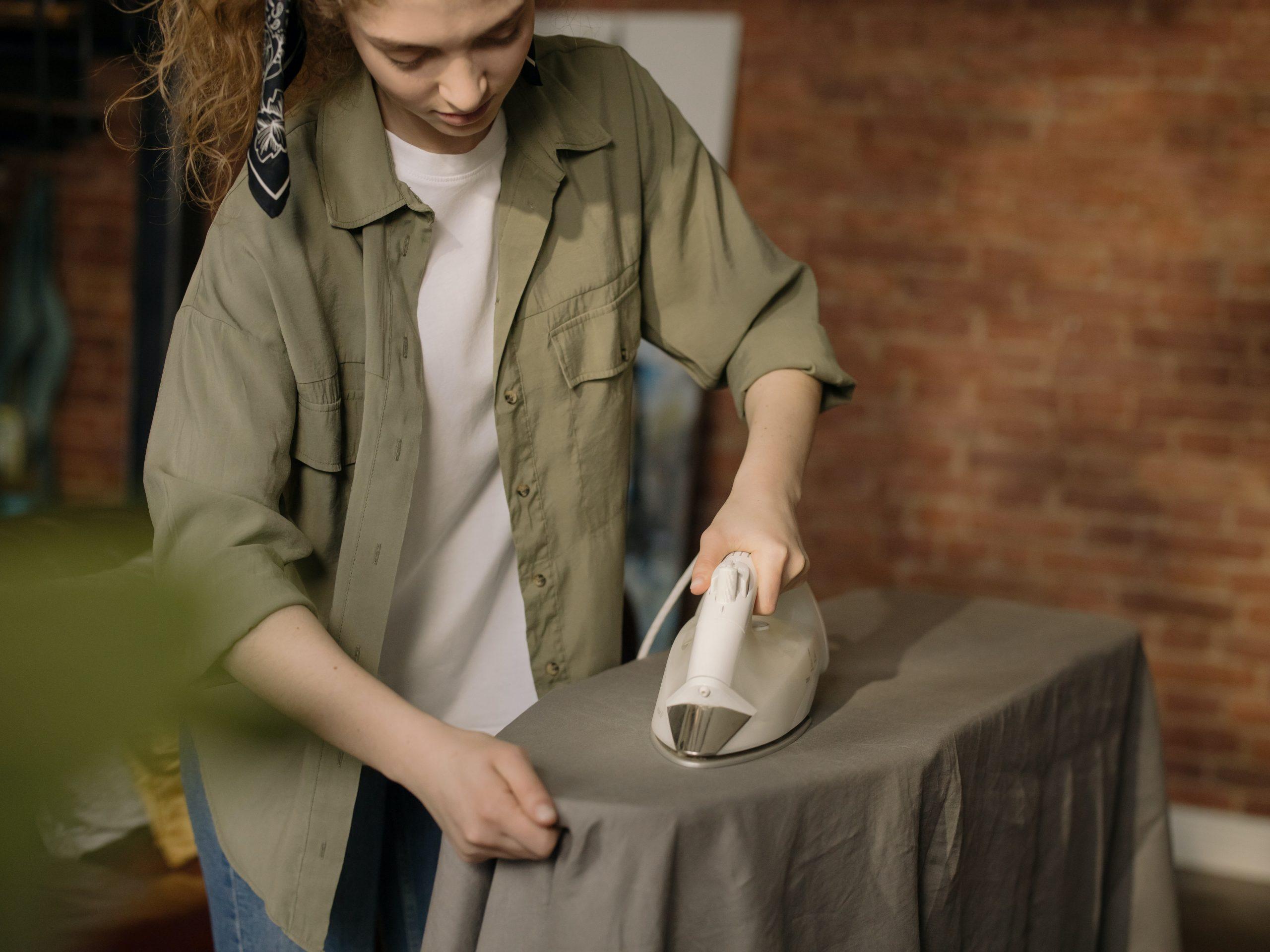 Na foto uma mulher passando roupa.