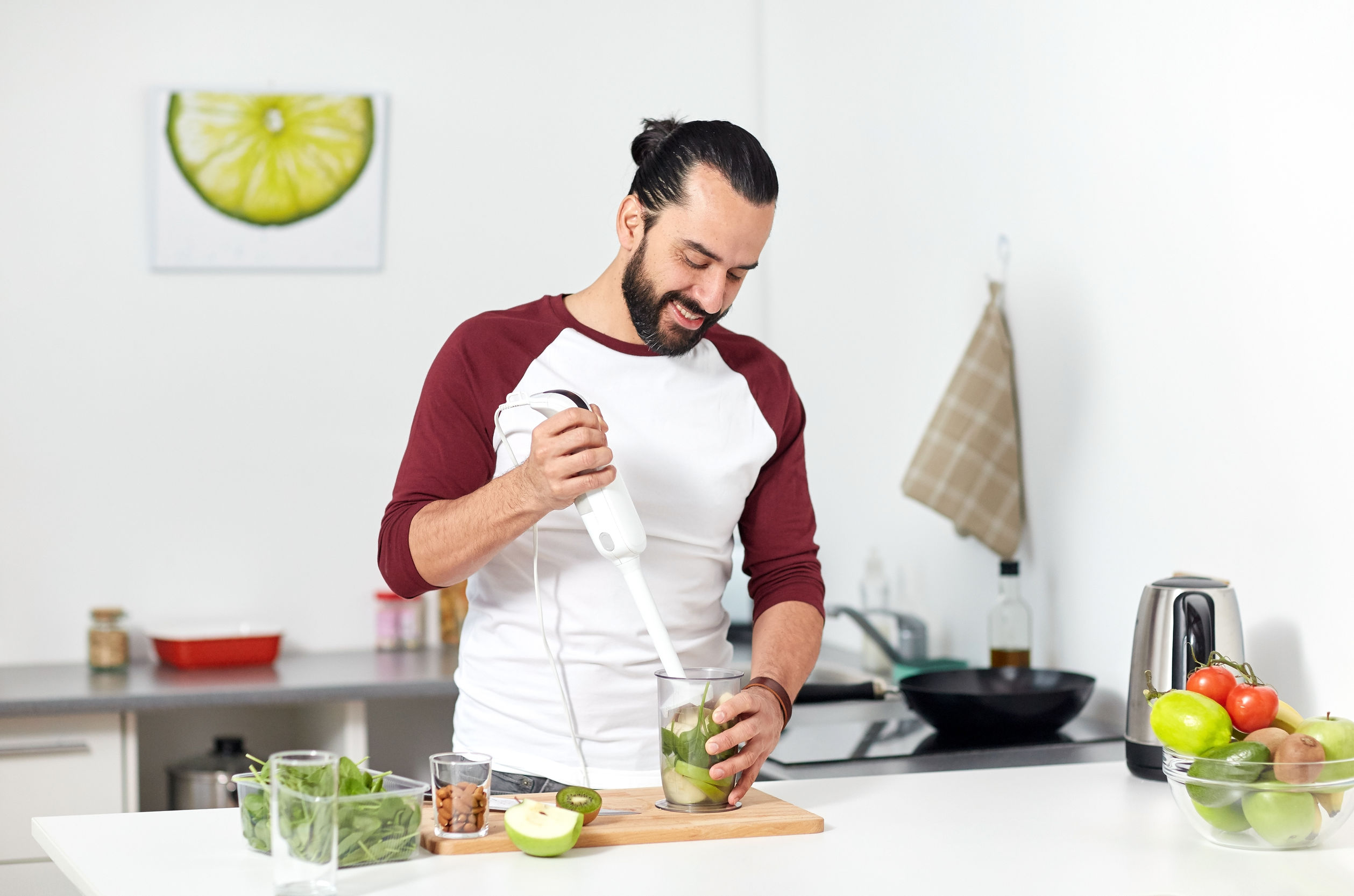 Homem jovem preparando suco de frutas com um mixer