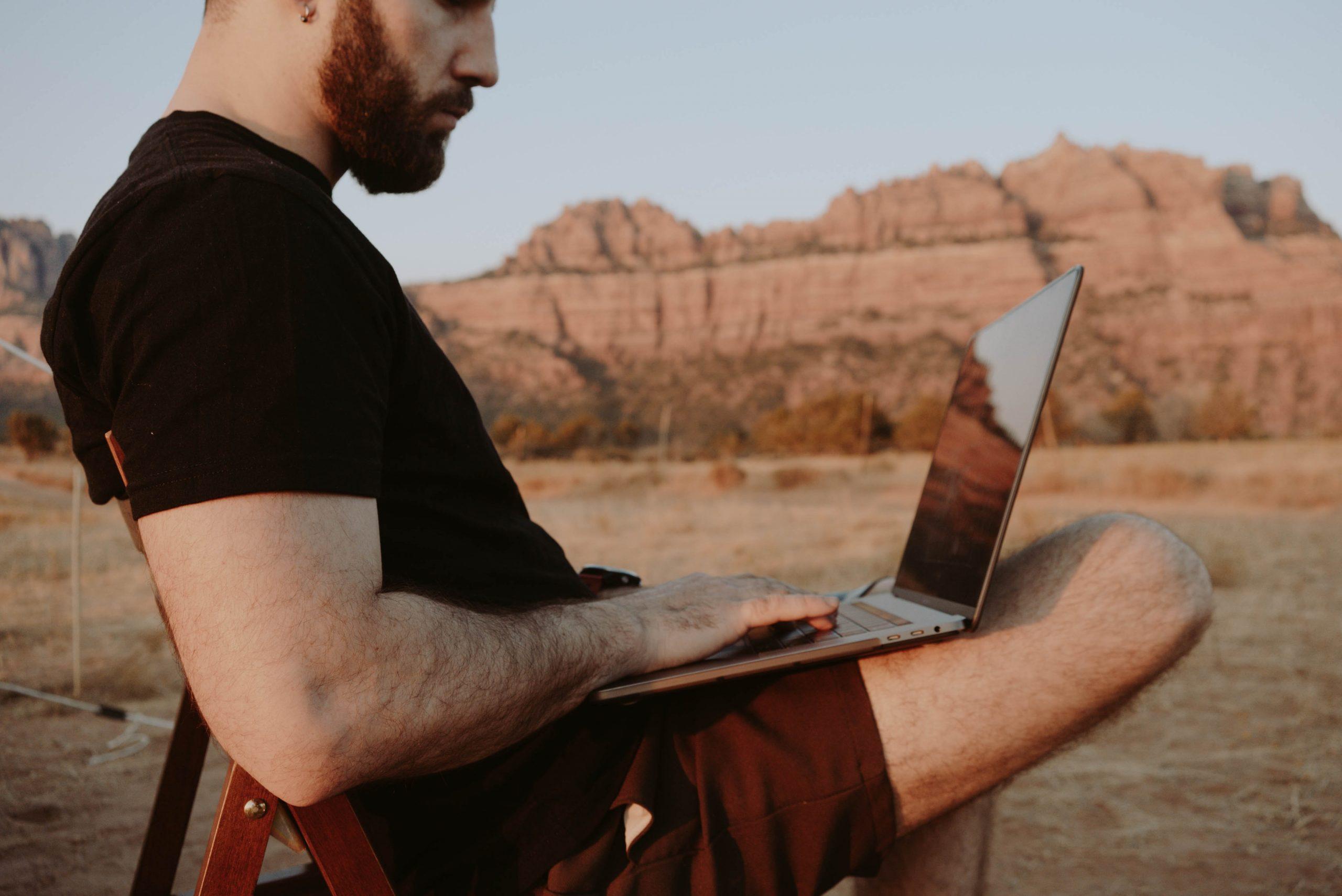 Imagem mostra um homem usando um notebook em meio à natureza.