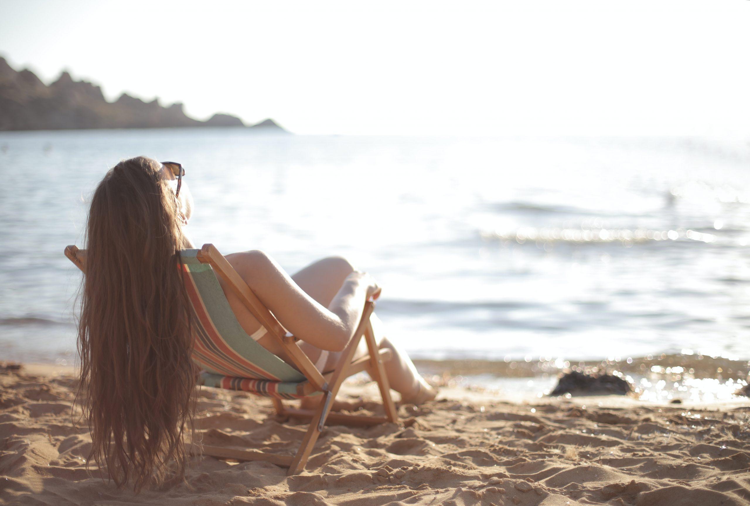 Na foto uma mulher sentada na beira da praia tomando sol.