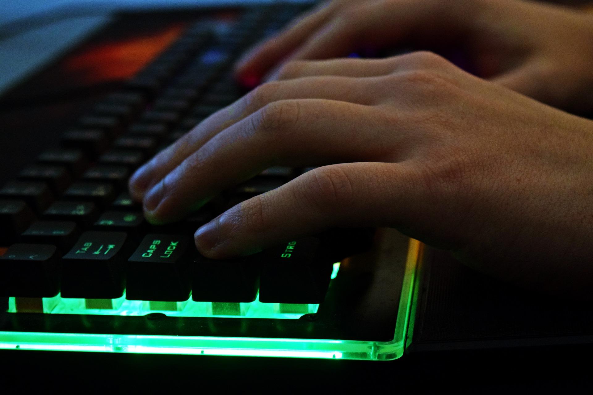 Imagem mostra um teclado gamer iluminado em uso.