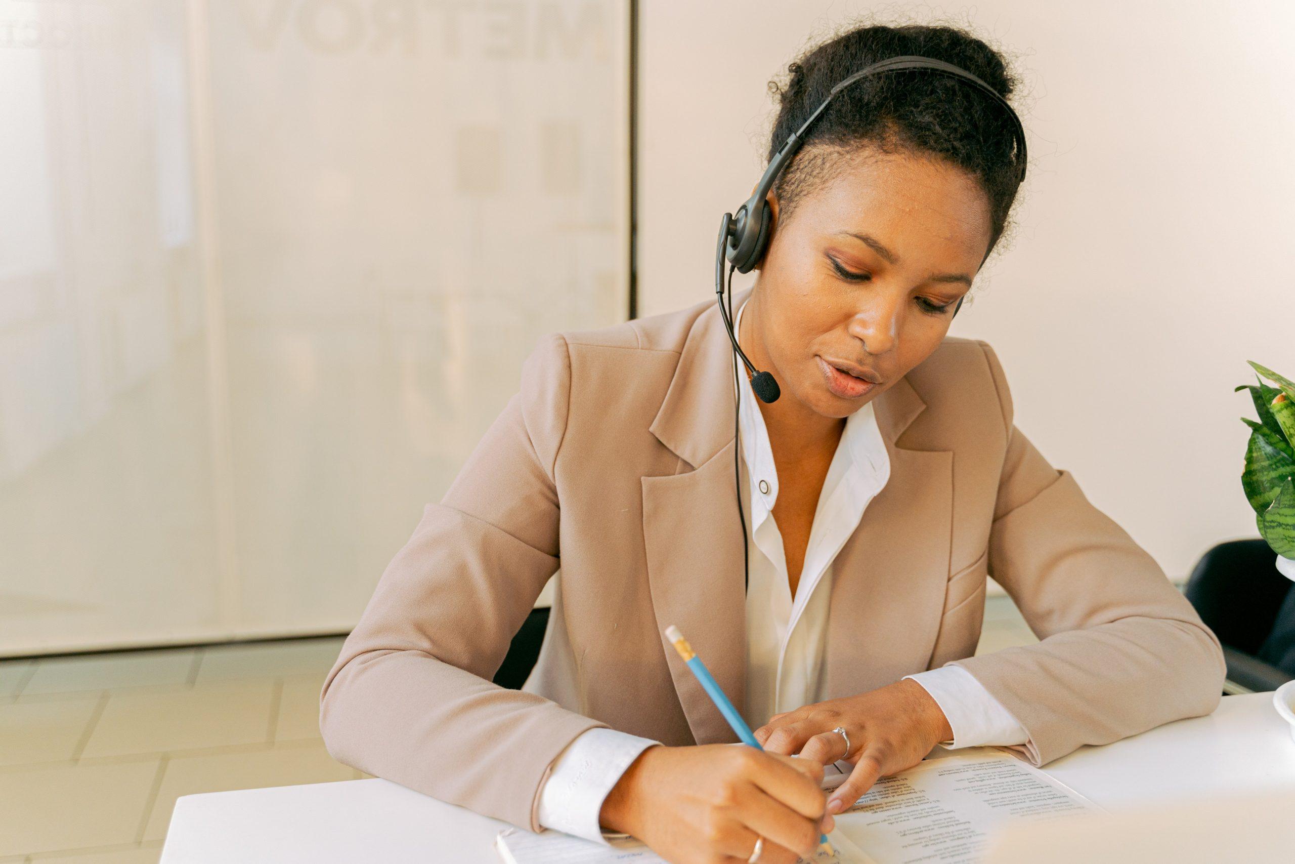 Imagem mostra mulher trabalhando sentada à sua mesa escrevendo enquanto usa um headset para falar ao telefone
