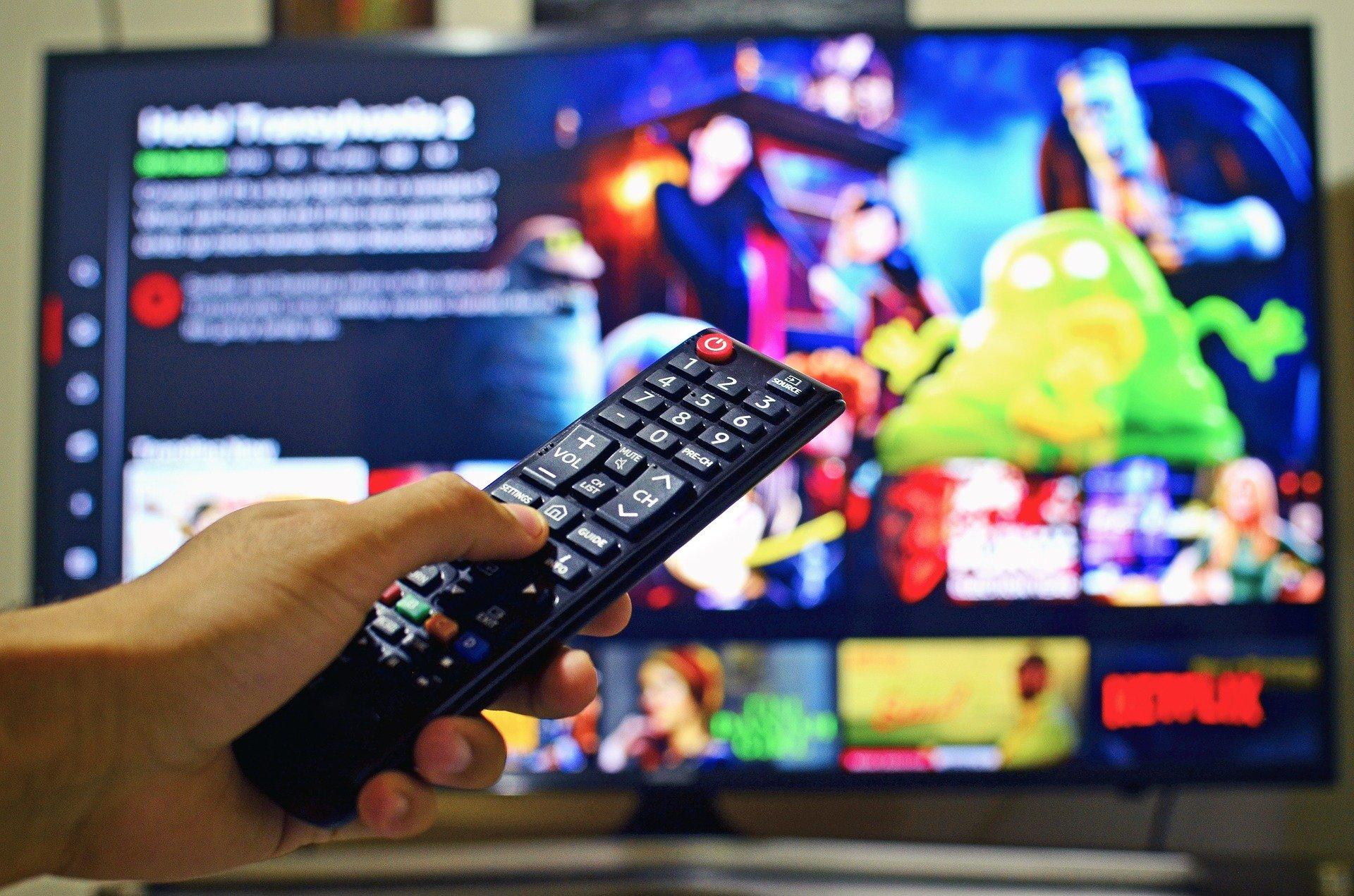 Na foto uma mão segurando um controle em frente a televisão.