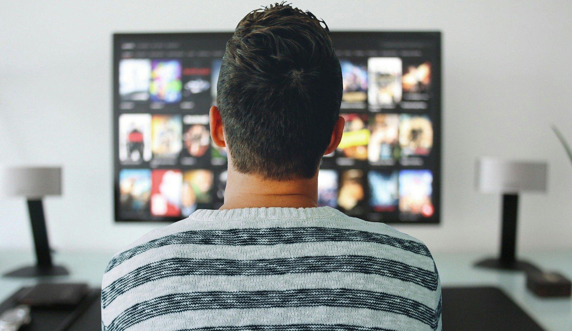 Na foto um homem de costas em frente a uma televisão.