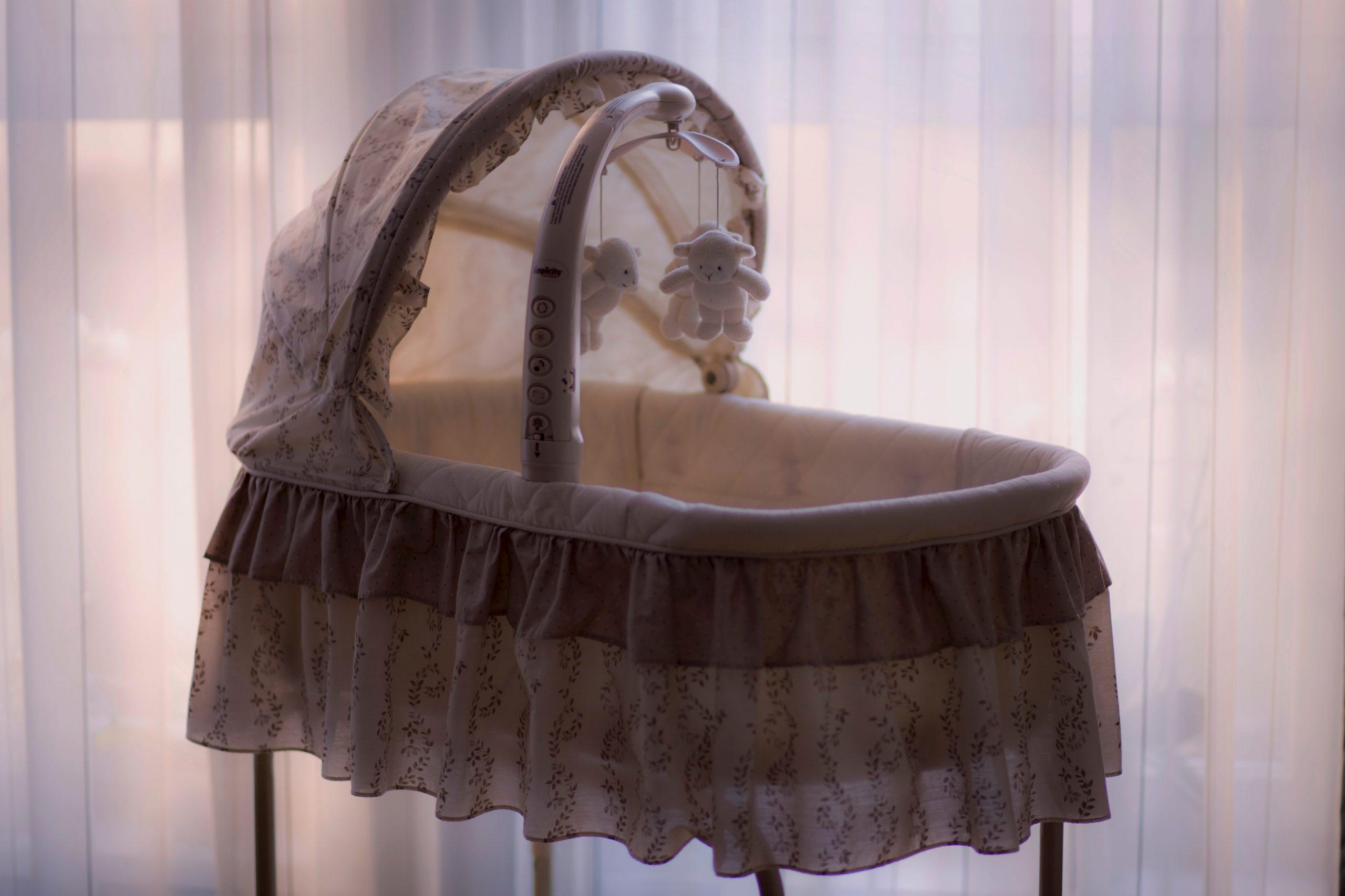 Na foto um berço de bebê com babados e um móbile de ovelhinhas.