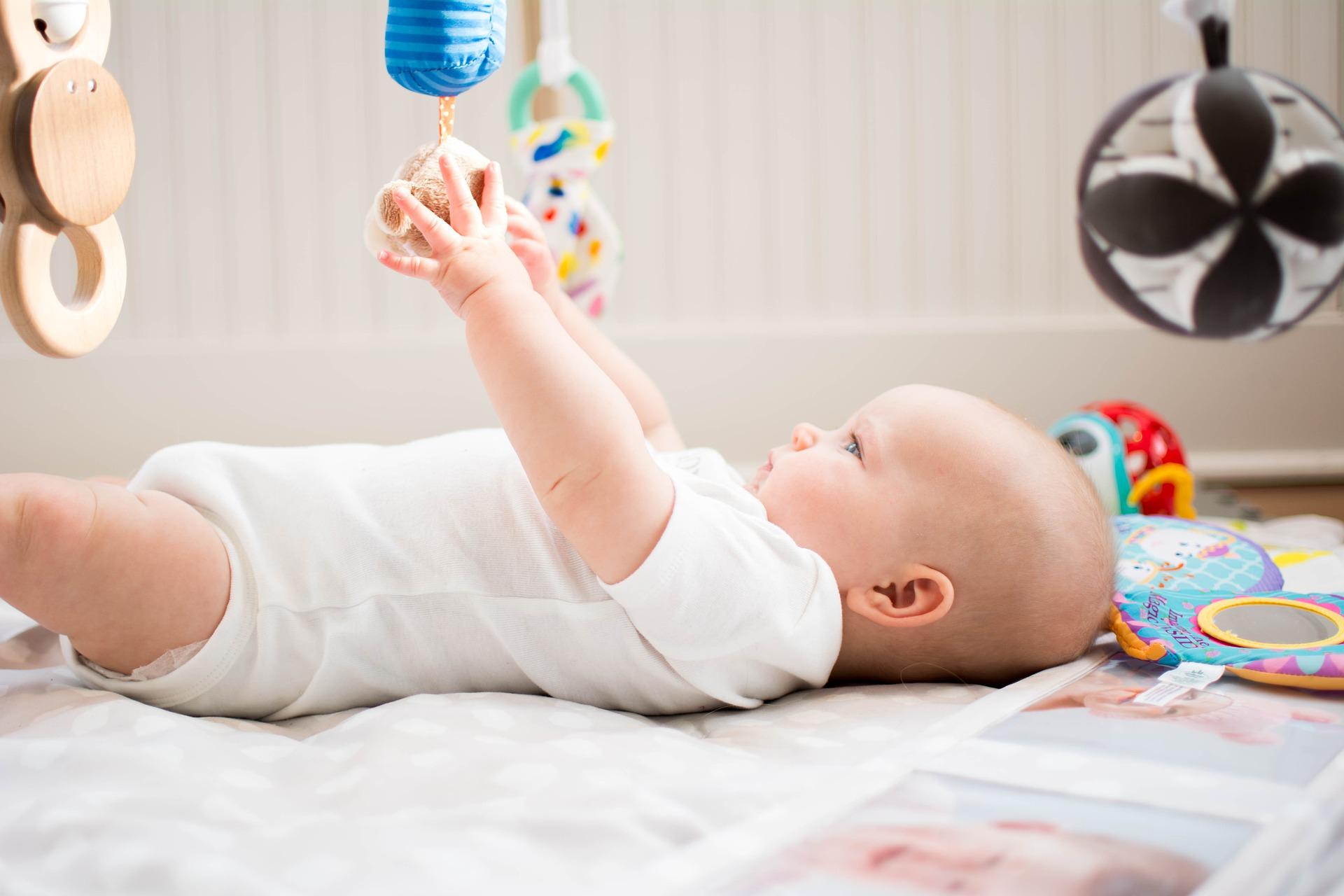 Na foto um bebê deitado brincando com um móbile.