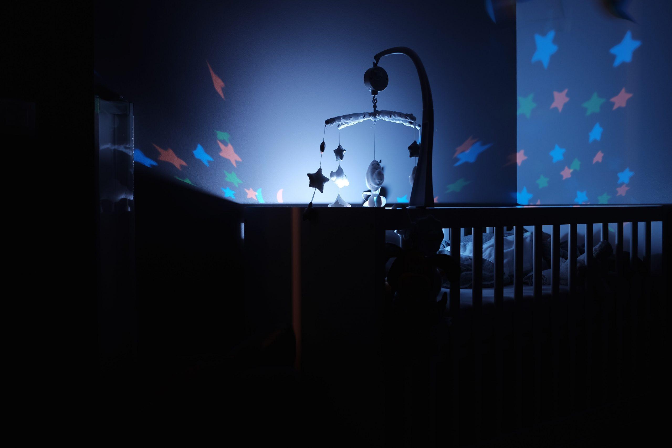 Na foto um berço em um quarto escuro com luzes em formato de estrela.