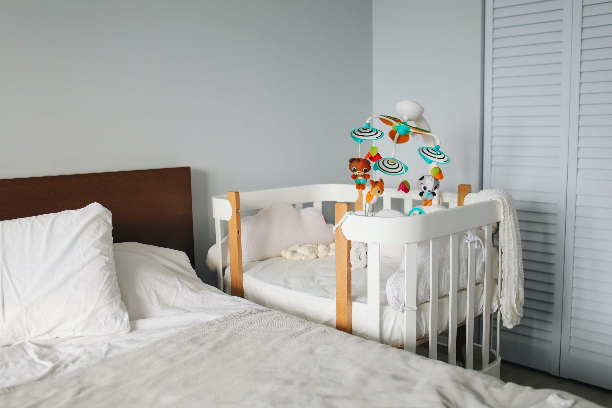 Na foto um quarto com uma cama e ao lado um berço de bebê.