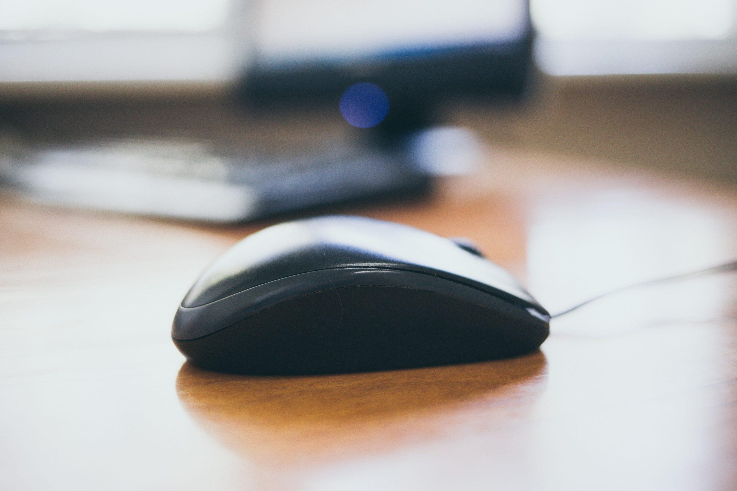 Imagem mostra um mouse sobre uma mesa.