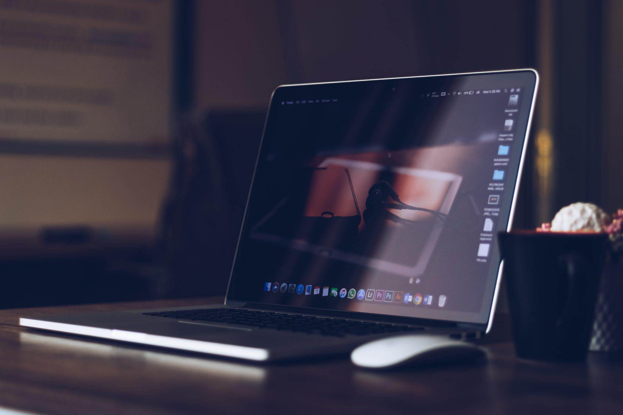 Imagem mostra um mouse ao lado de um notebook.