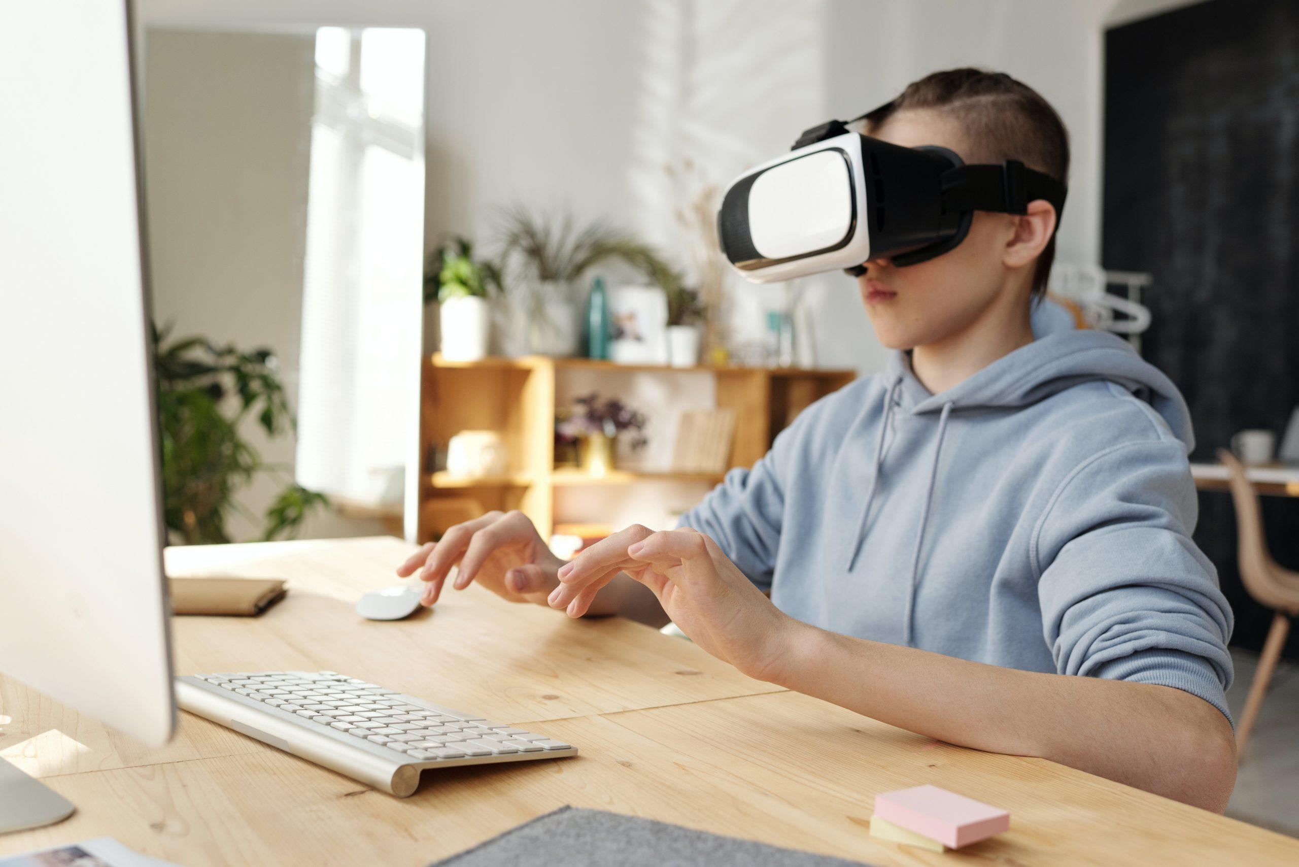 Imagem mostra uma criança com um óculos VR em frente a um computador.
