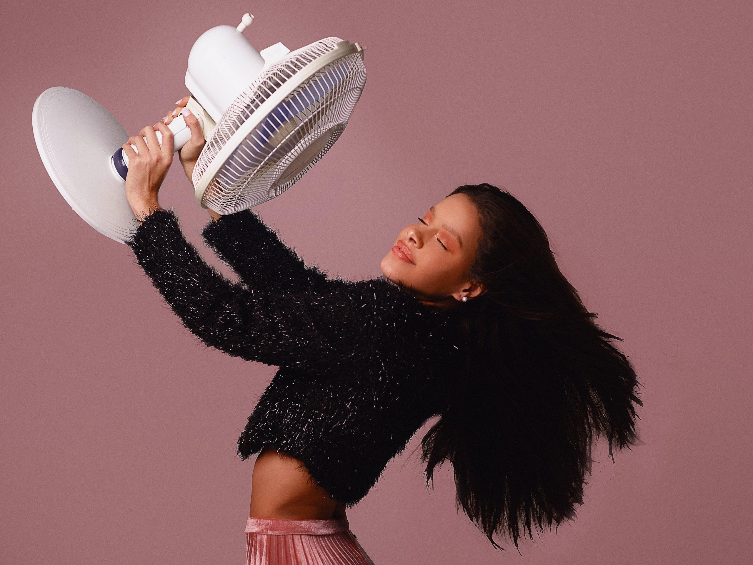Imagem de uma mulher segurando um ventilador.