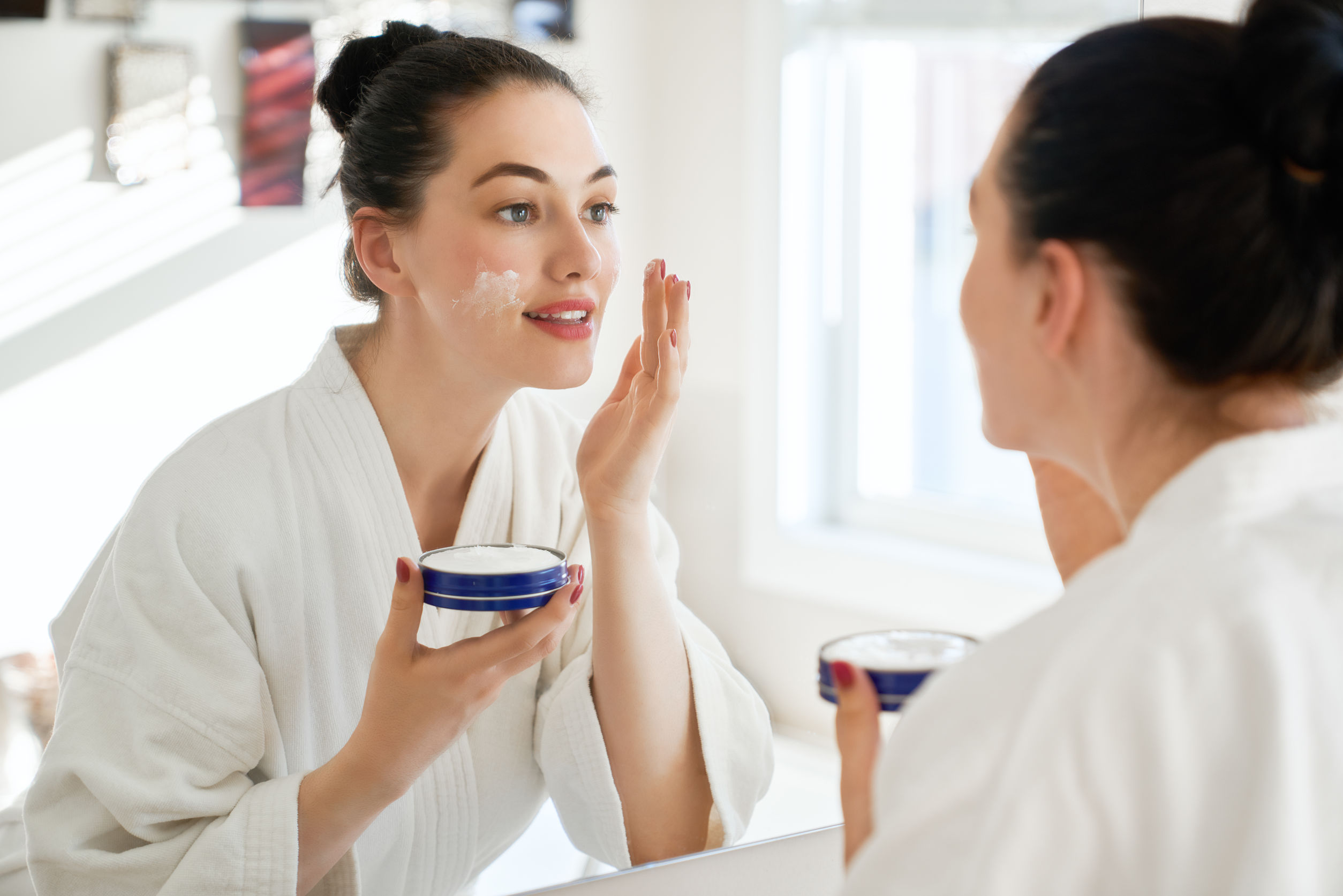 Mulher com toalha de banho na cabeça passando creme no rosto.