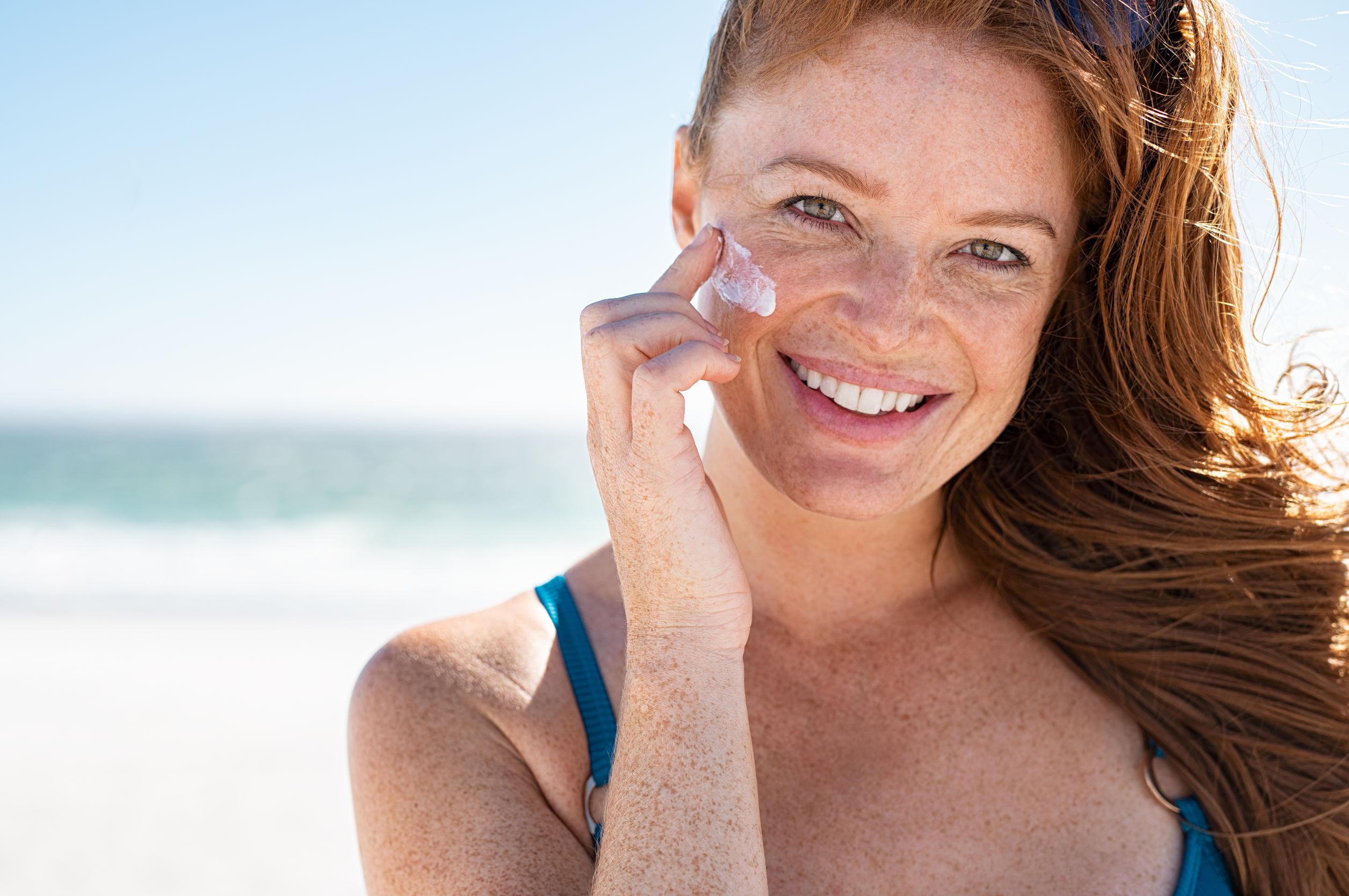 Mulher na praia passando protetor solar no rosto.