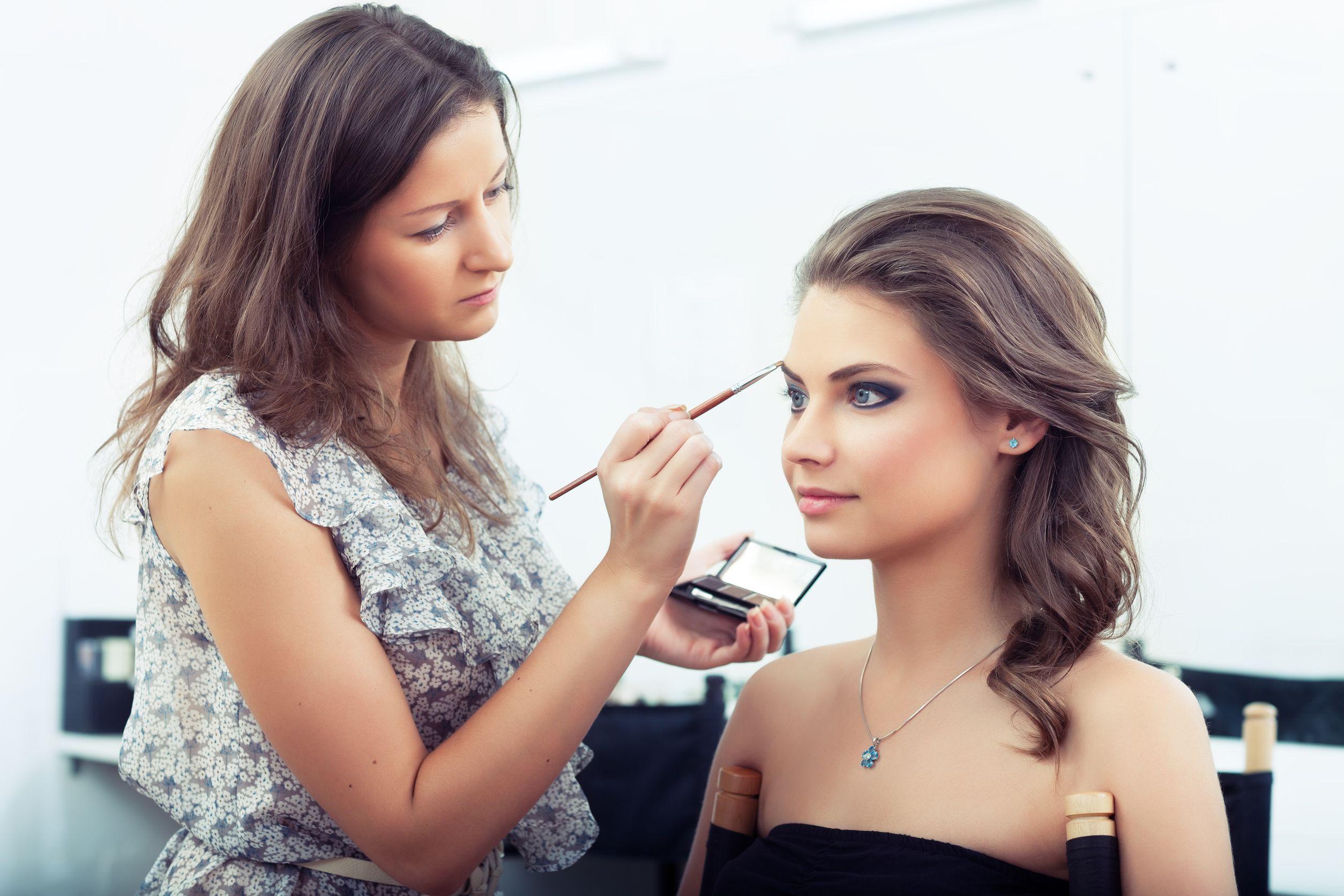 Maquiadora passando delineador em uma mulher de olhos fechados. Elas estão em um salão de beleza.