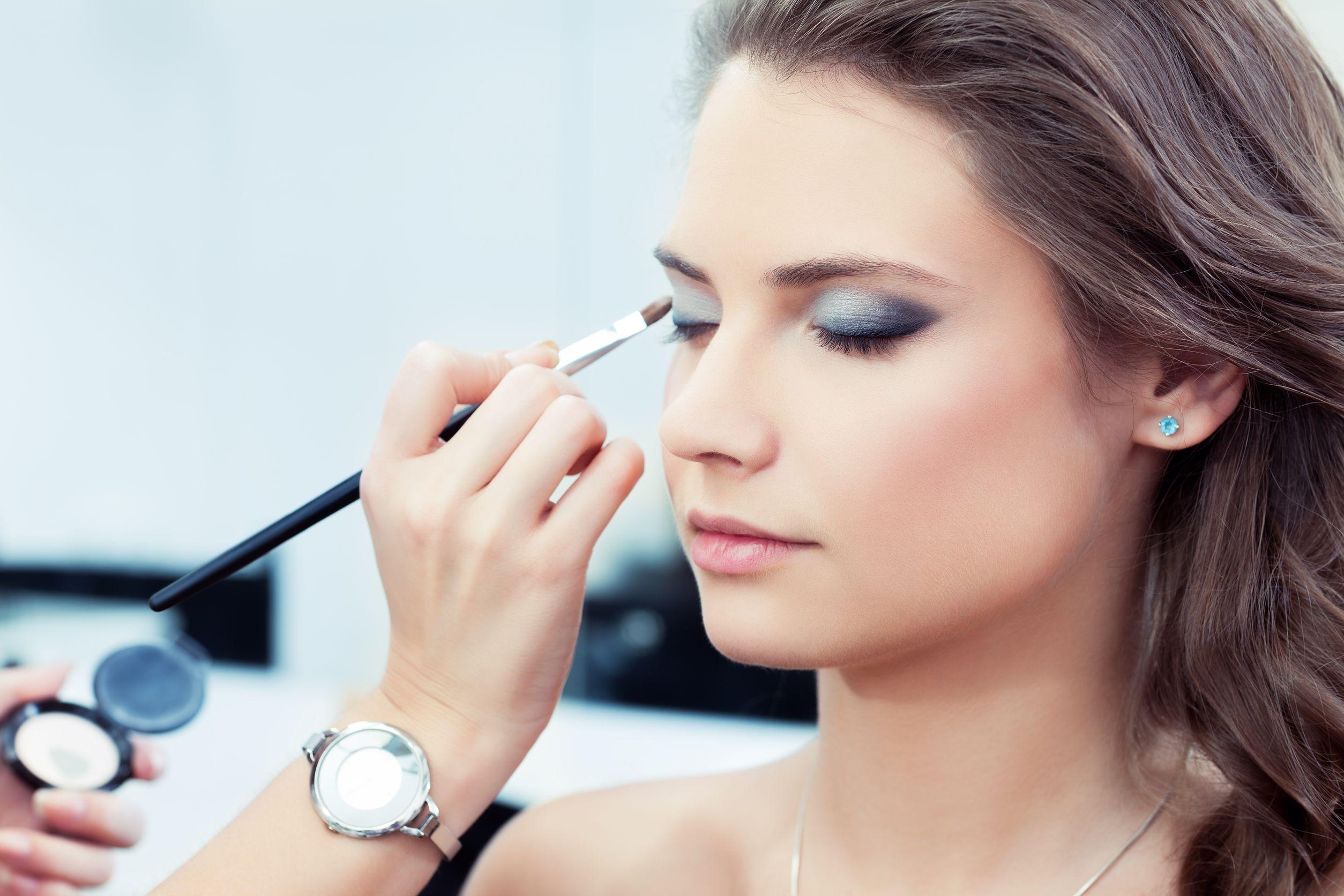 Mulher de olhos fechados, passando delineador, sentada em uma mesa com produtos de maquiagem.