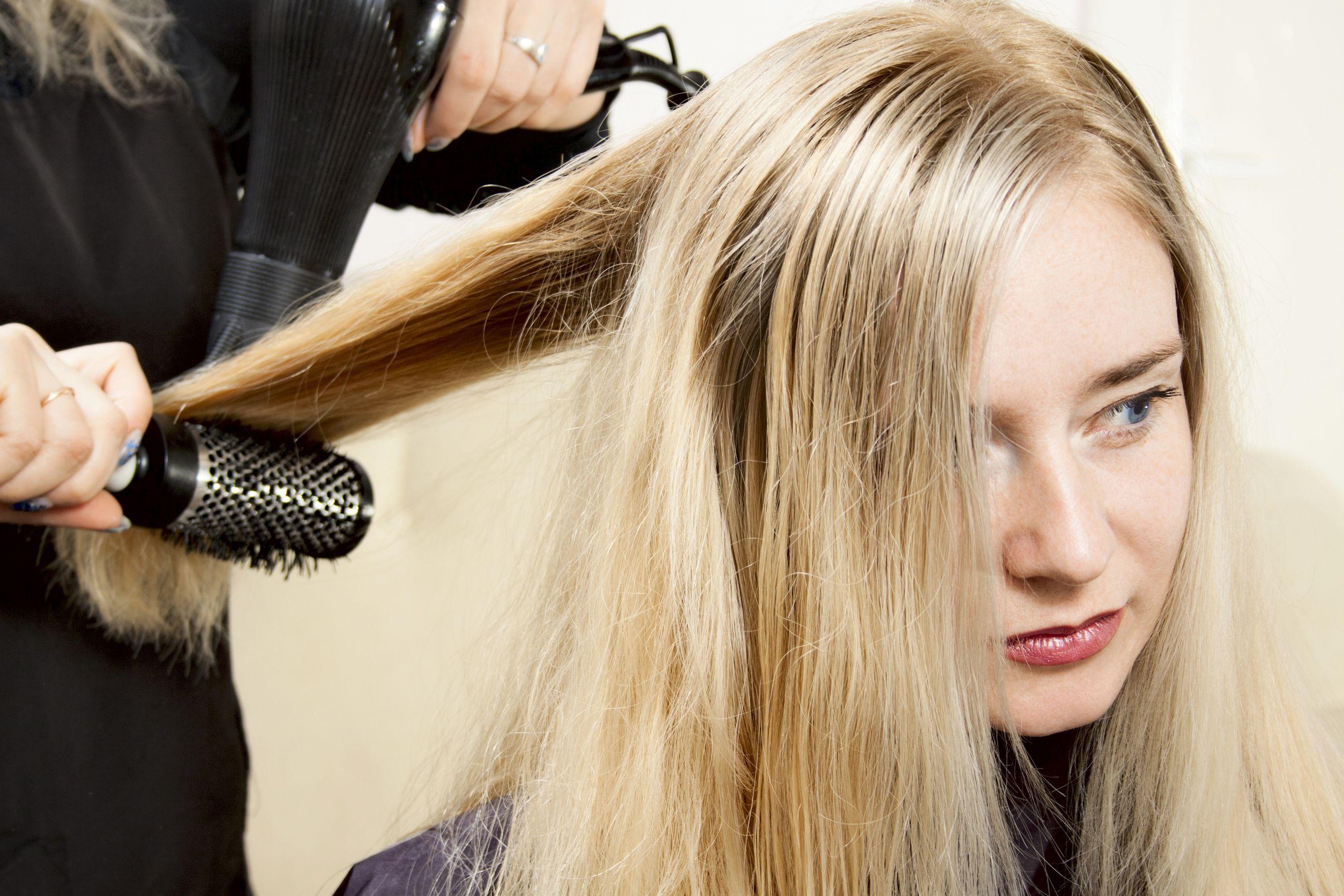 Cabelereira secando cabelo de uma mulher com secador e escova em um salão de beleza.