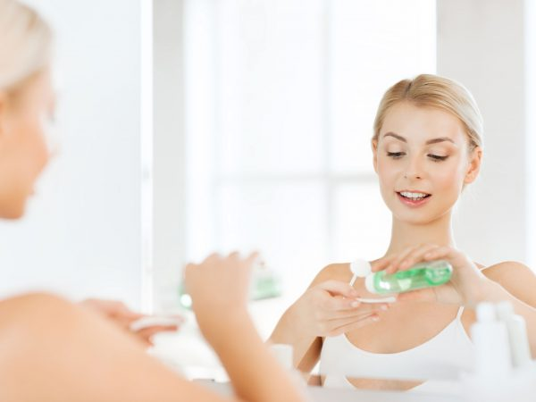 beauty, skin care and people concept – smiling young woman applying lotion to cotton disc for washing her face at bathroom