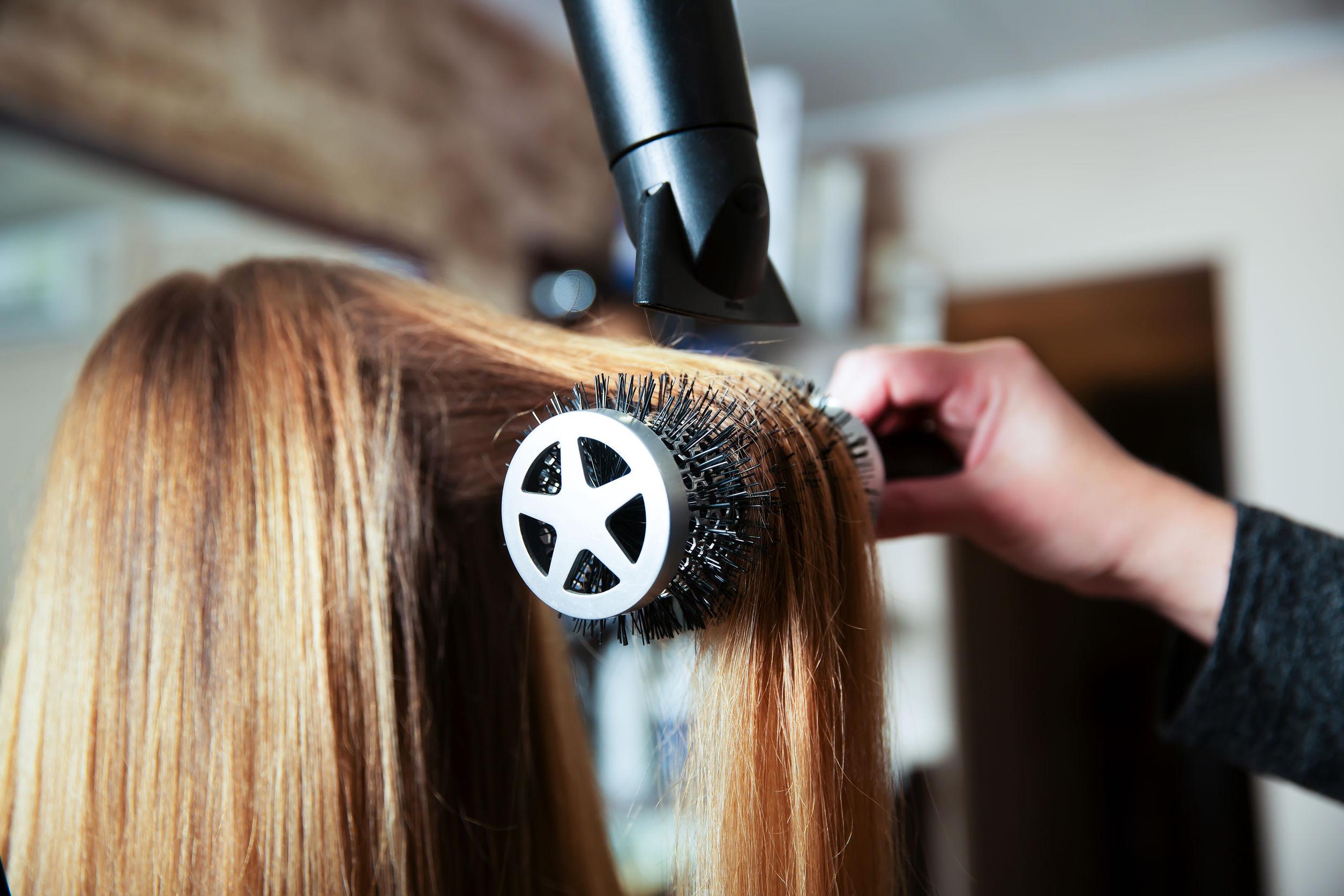 Mulher arrumando o cabelo de uma cliente com um secador verde e uma escova branca