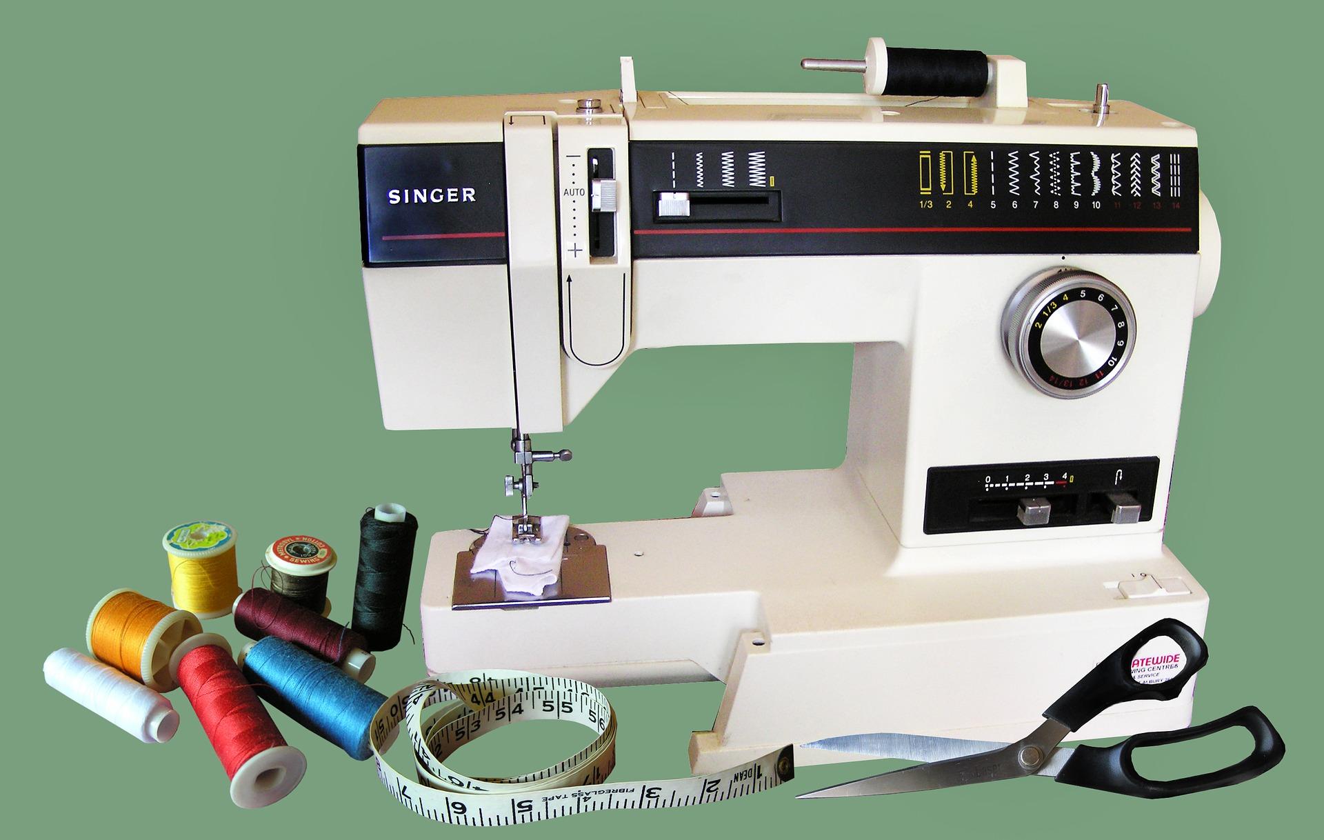 Máquina de costura, tesoura, fita métrica e linhas.